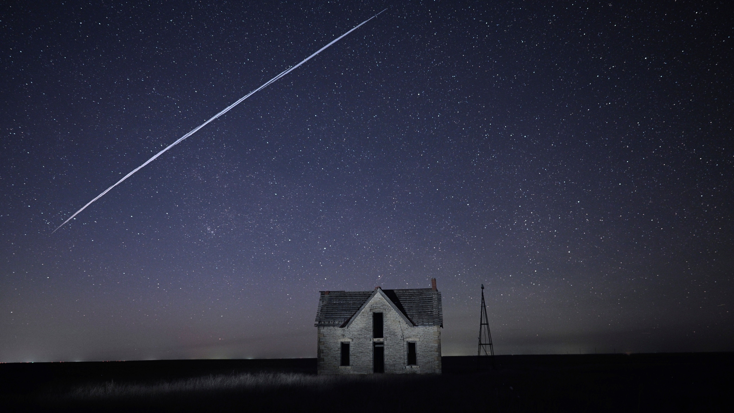 In this photo taken May 6, 2021, with a long exposure, a string of SpaceX StarLink satellites passes over an old stone house near Florence, Kan. The train of lights was actually a series of relatively low-flying satellites launched by Elon Musk's SpaceX as part of its Starlink internet service earlier this week. (AP Photo/Reed Hoffmann, File)