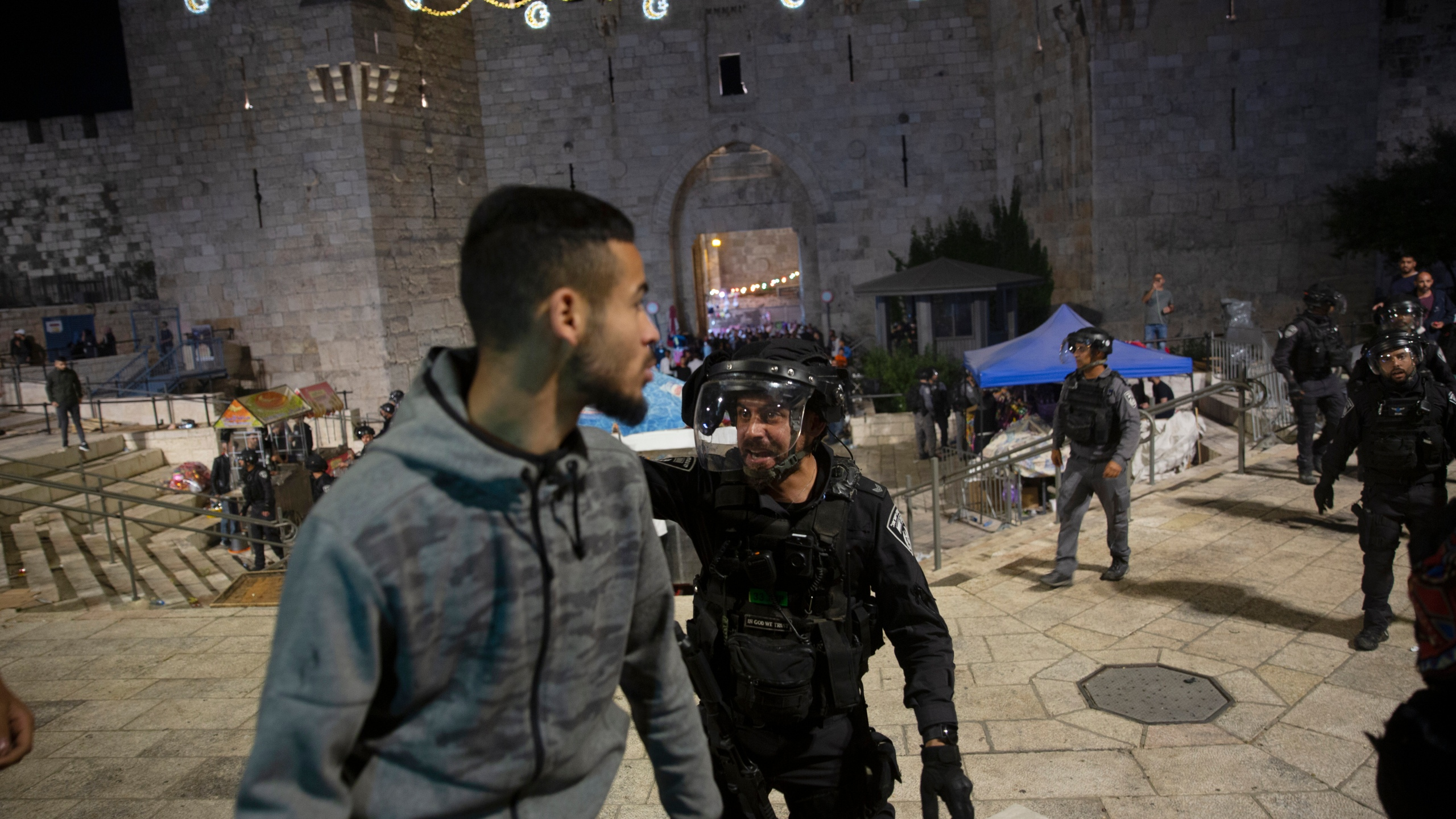 An Israeli policeman shouts at a Palestinian man to leave the Damascus Gate to the Old City of Jerusalem after clashes at the Al-Aqsa Mosque compound on May 7, 2021. (Maya Alleruzzo / Associated Press)