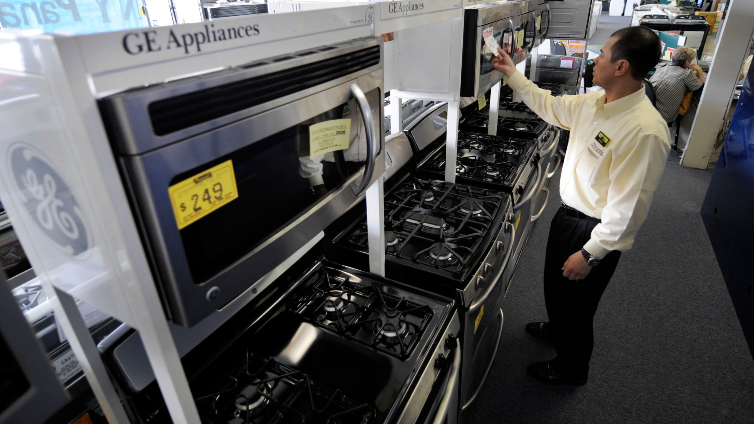 In this April 8, 2008, file photo, salesman Hank Pham puts the price on a General Electric microwave oven in the appliances section of Howard's Appliance and Big-Screen Superstore in San Gabriel, Calif. The California Energy Commission released a draft building standards code Thursday, May 6, 2021, that would require new homes to be equipped with circuits and panels that support all-electric appliances for heating, cooking and drying clothes. While the code doesn't explicitly forbid gas, the commission hopes it will lead builders to construct all-electric structures as part of a growing effort to eliminate fossil fuels from buildings, which account for about one-quarter of the state's annual greenhouse gas emissions. (AP Photo/Kevork Djansezian, File)
