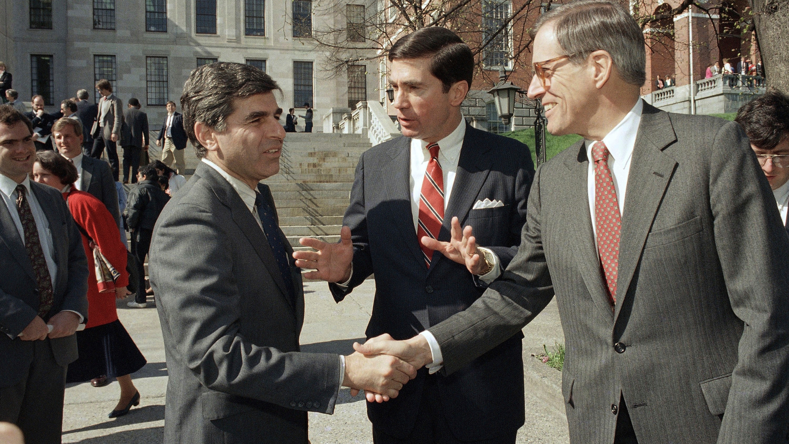 In this April 27, 1987, file photo, Massachusetts Governor Michael Dukakis, left, shakes the hands of former Delaware Governor Pierre Du Pont, right as former Virginia Governor Charles S. Robb looks on, after both men attended the Jobs for Bay State Grads program in Boston. (AP Photo/Jim Shea, File)