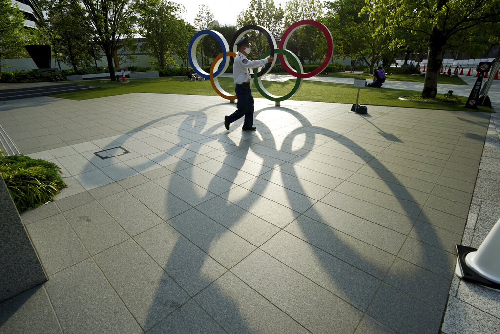 A security guard wearing a protective mask to help curb the spread of the coronavirus walks in front of the Olympic Rings on May 9, 2021, in Tokyo. (AP Photo/Eugene Hoshiko)