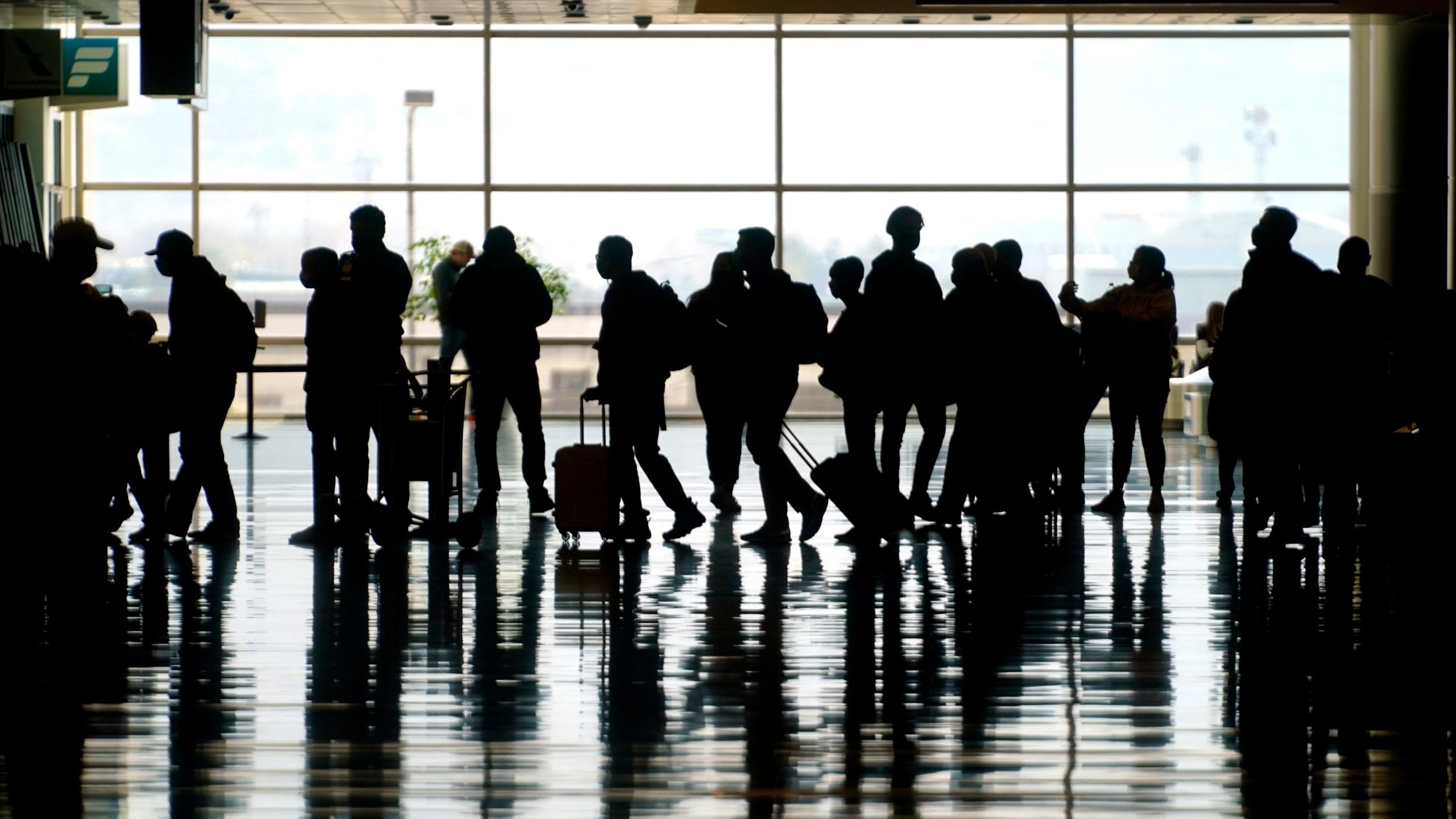 Travelers walk through the Salt Lake City International Airport in Salt Lake City on March 17, 2021. (Rick Bowmer / Associated Press)
