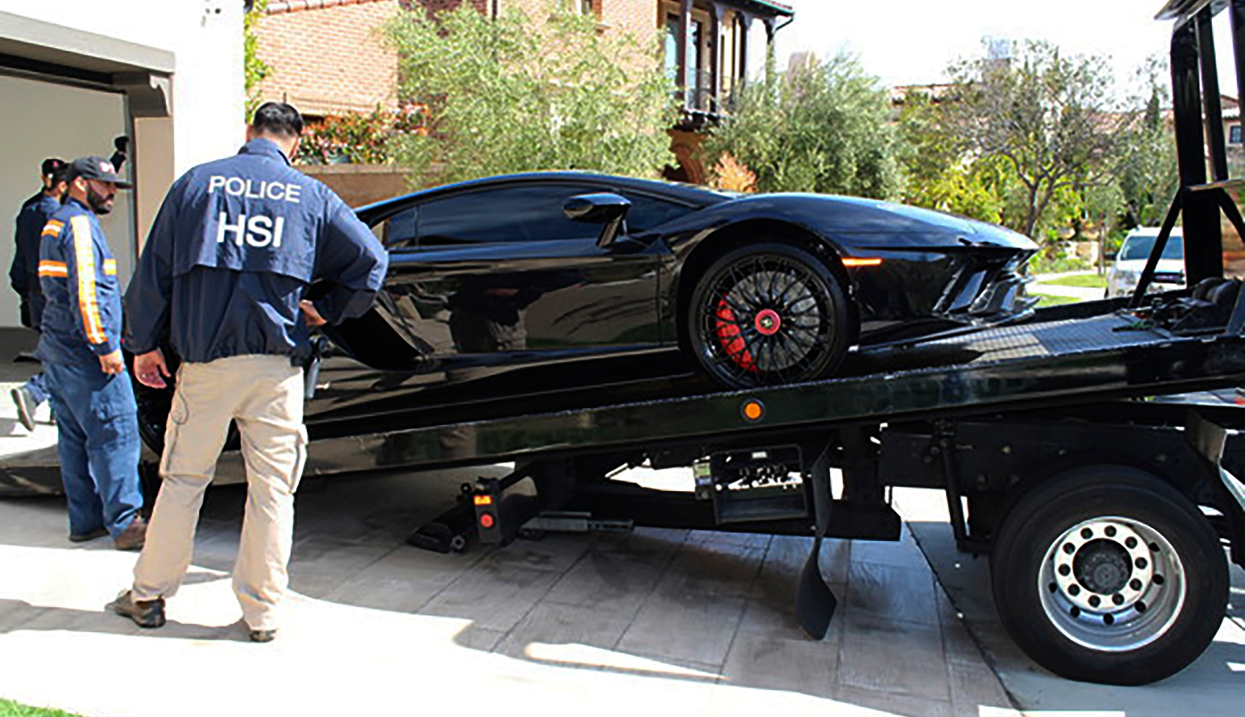 This photo provided by U.S. Immigration and Customs Enforcement shows a special agent with HSI Los Angeles's El Camino Real Financial Crimes Task Force seize a Ferrari from Orange County businessman Mustafa Qadiri on April 7, 2021, in Santa Ana, Calif. (U.S. Immigration and Customs Enforcement via AP)