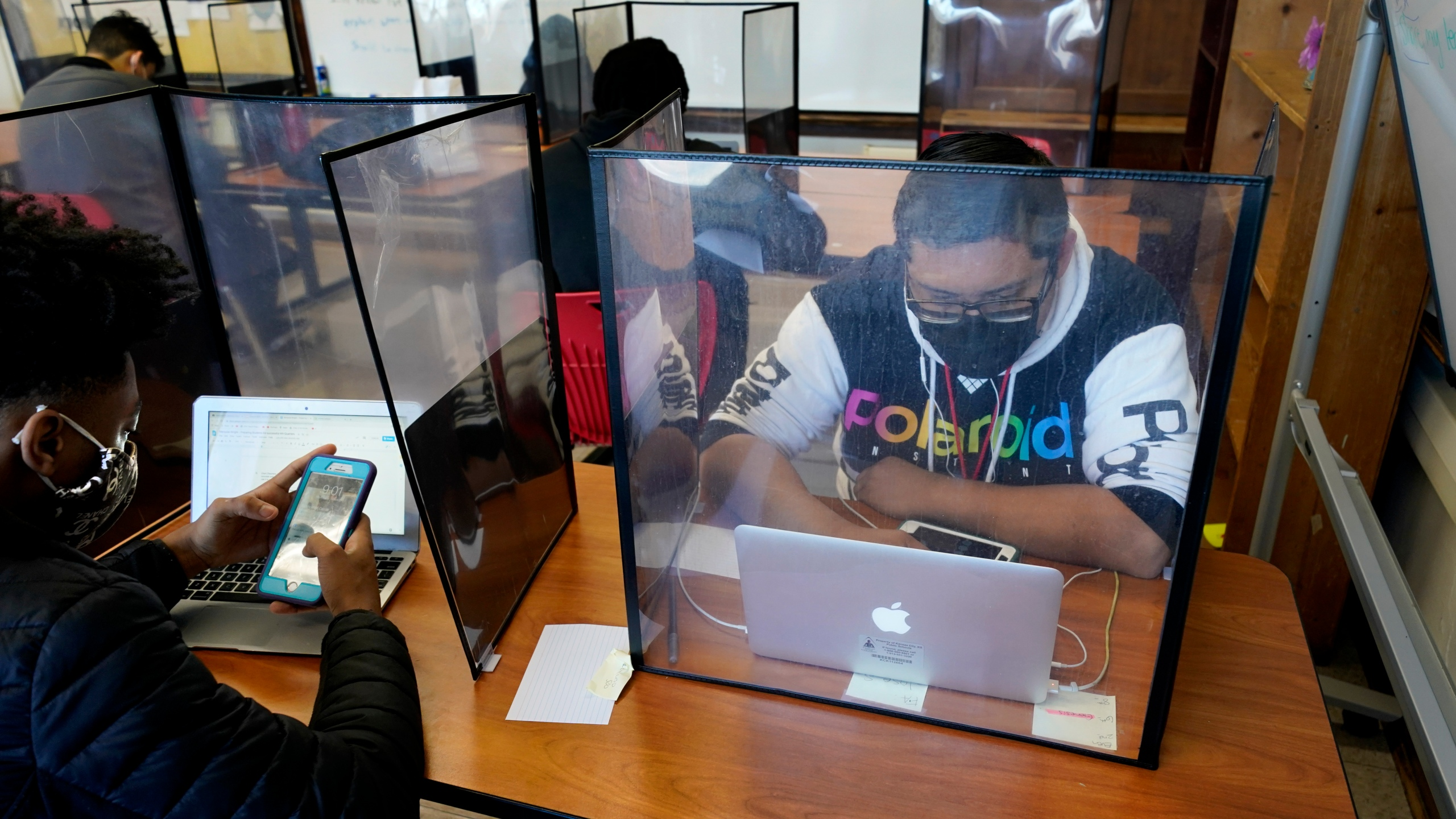 Senior Jose Solano-Hernandez, right, studies with classmates on the first day of in-person learning at Wyandotte High School in Kansas City, Kan., Wednesday, March 30, 2021. (AP Photo/Charlie Riedel)