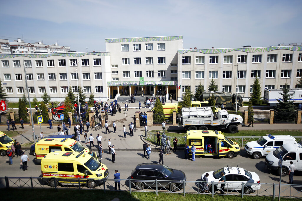 Ambulances and police cars and a truck are parked at a school after a shooting in Kazan, Russia, Tuesday, May 11, 2021. (AP Photo/Roman Kruchinin)