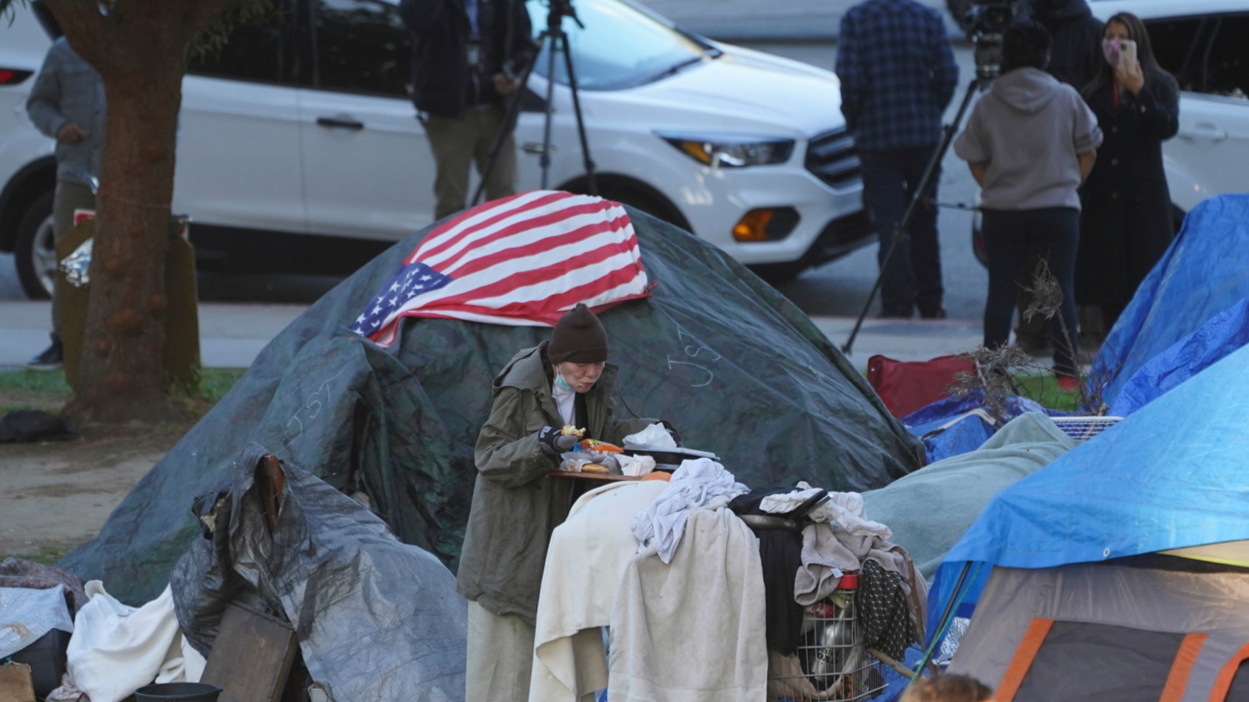 In this March 24, 2021, file photo a woman eats at her tent at the Echo Park homeless encampment at Echo Park Lake in Los Angeles. (AP Photo/Damian Dovarganes, File)