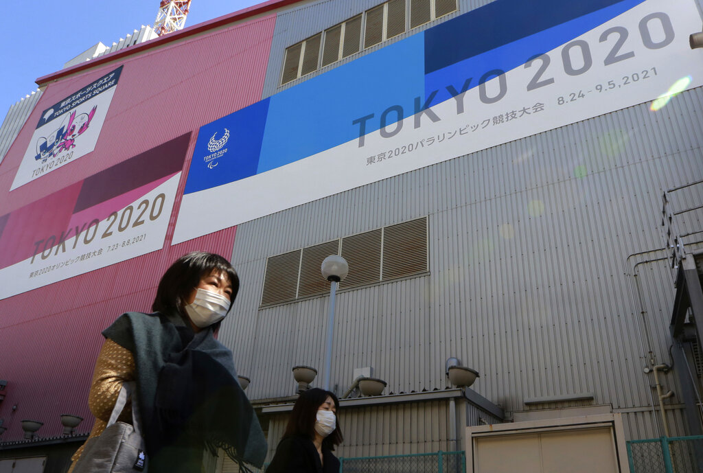 In this Feb. 24, 2021, file photo, people walk past posters to promote the Olympic Games scheduled to start in the summer in Tokyo. (AP Photo/Koji Sasahara, File)