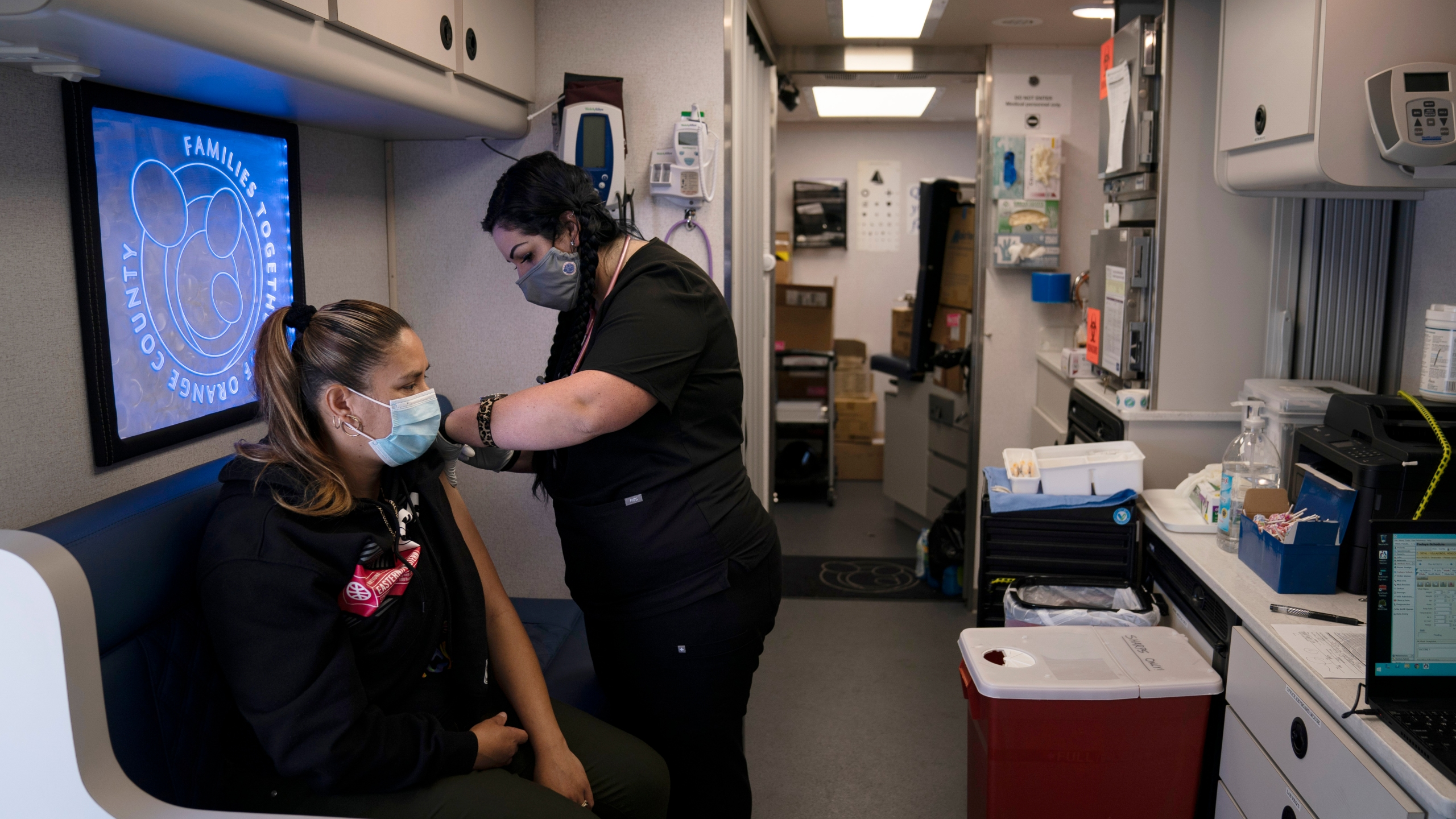 In this April 29, 2021, file photo, nurse Natasha Garcia administers a dose of the Moderna COVID-19 vaccine to Monica Villalobos in a mobile clinic set up in the parking lot of a shopping center in Orange, Calif. COVID-19 deaths in the U.S. have tumbled to an average of just over 600 per day — the lowest level in 10 months — with the number of lives lost dropping to single digits in well over half the states and hitting zero on some days. (AP Photo/Jae C. Hong, File)