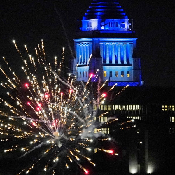 Los Angeles City Hall is illuminated with dark blue lights as Dodgers fans celebrate with fireworks on Sunset Boulevard after watching Game 6 of the World Series on Oct. 27, 2020. (Damian Dovarganes / Associated Press)