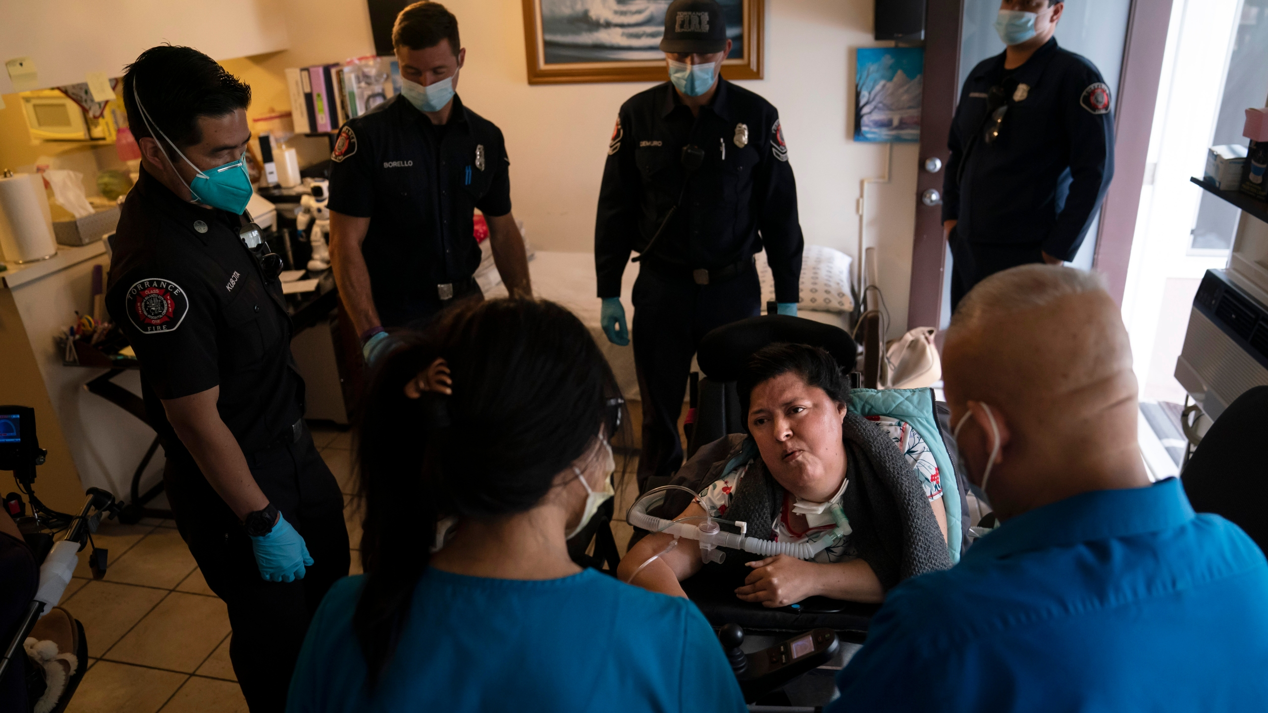 Socorro Franco-Martinez, seated, who suffers from muscular dystrophy, is surrounded by Torrance firefighters as she talks with pharmacist Stella Kim, foreground left, after getting her second dose of the Pfizer COVID-19 vaccine in her apartment, Wednesday, May 12, 2021, in Torrance, Calif. Teamed up with the Torrance Fire Department, Torrance Memorial Medical Center started inoculating people at home in March, identifying people through a city hotline, county health department, senior centers and doctor's offices, said Mei Tsai, the pharmacist who coordinates the program. (AP Photo/Jae C. Hong)