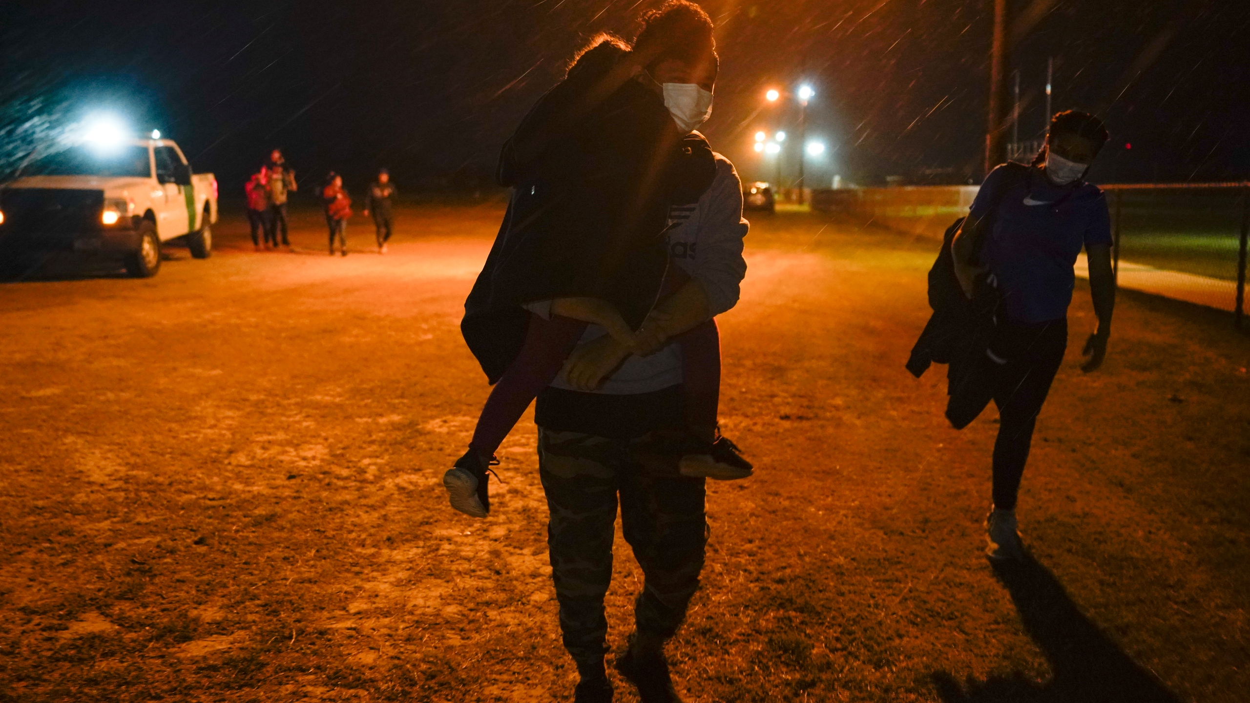 A migrant carries a child at an intake area after turning themselves in upon crossing the U.S.-Mexico border, late Tuesday, May 11, 2021, in La Joya, Texas. The U.S. government continues to report large numbers of migrants crossing the U.S.-Mexico border with an increase in adult crossers. But families and unaccompanied children are still arriving in dramatic numbers despite the weather changing in the Rio Grande Valley registering hotter days and nights. (AP Photo/Gregory Bull)