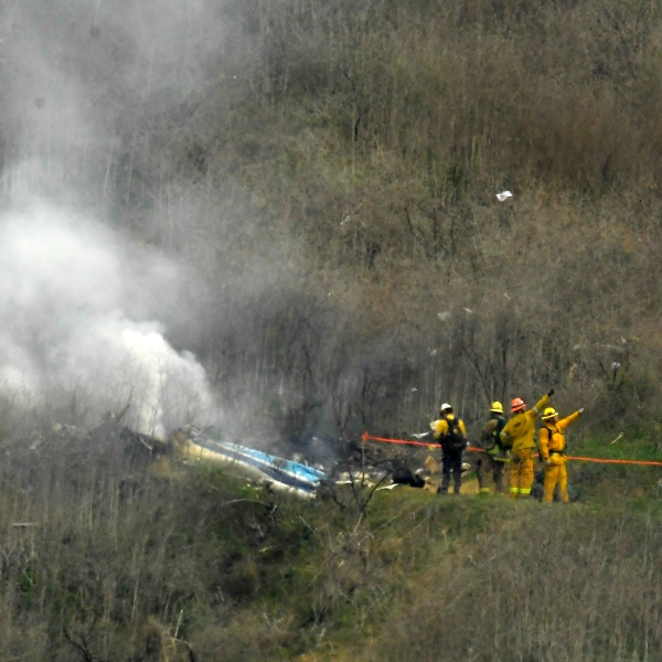 In this Jan. 26, 2020 file photo firefighters work the scene of a helicopter crash where former NBA basketball star Kobe Bryant died, in Calabasas. Two Los Angeles County firefighters could be fired and a third suspended in the fallout over first responders sharing graphic photos from the site of the helicopter crash that killed Bryant, his teenage daughter and seven others, court documents say. The court documents were filed May 10, 2021, as part of widow Vanessa Bryant's federal lawsuit against Los Angeles County that alleges invasion of privacy. (Mark J. Terrill/Associated Press)
