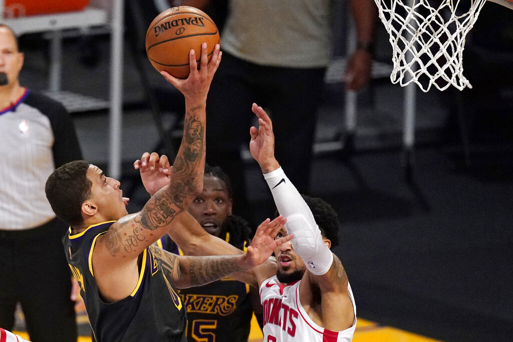Los Angeles Lakers forward Kyle Kuzma, left, shoots and scores as Houston Rockets forward Kenyon Martin Jr., right, defends in the closing seconds of the second half of an NBA basketball game Wednesday, May 12, 2021, in Los Angeles. (AP Photo/Mark J. Terrill)