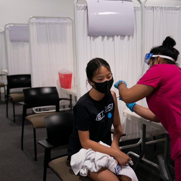 Melody Chuang, 14, receives her first dose of the Pfizer COVID-19 vaccine from medical assistant Gloria Urgell at Providence Edwards Lifesciences vaccination site in Santa Ana, Calif., Thursday, May 13, 2021. The state began vaccinating children ages 12 to 15 Thursday. (AP Photo/Jae C. Hong)