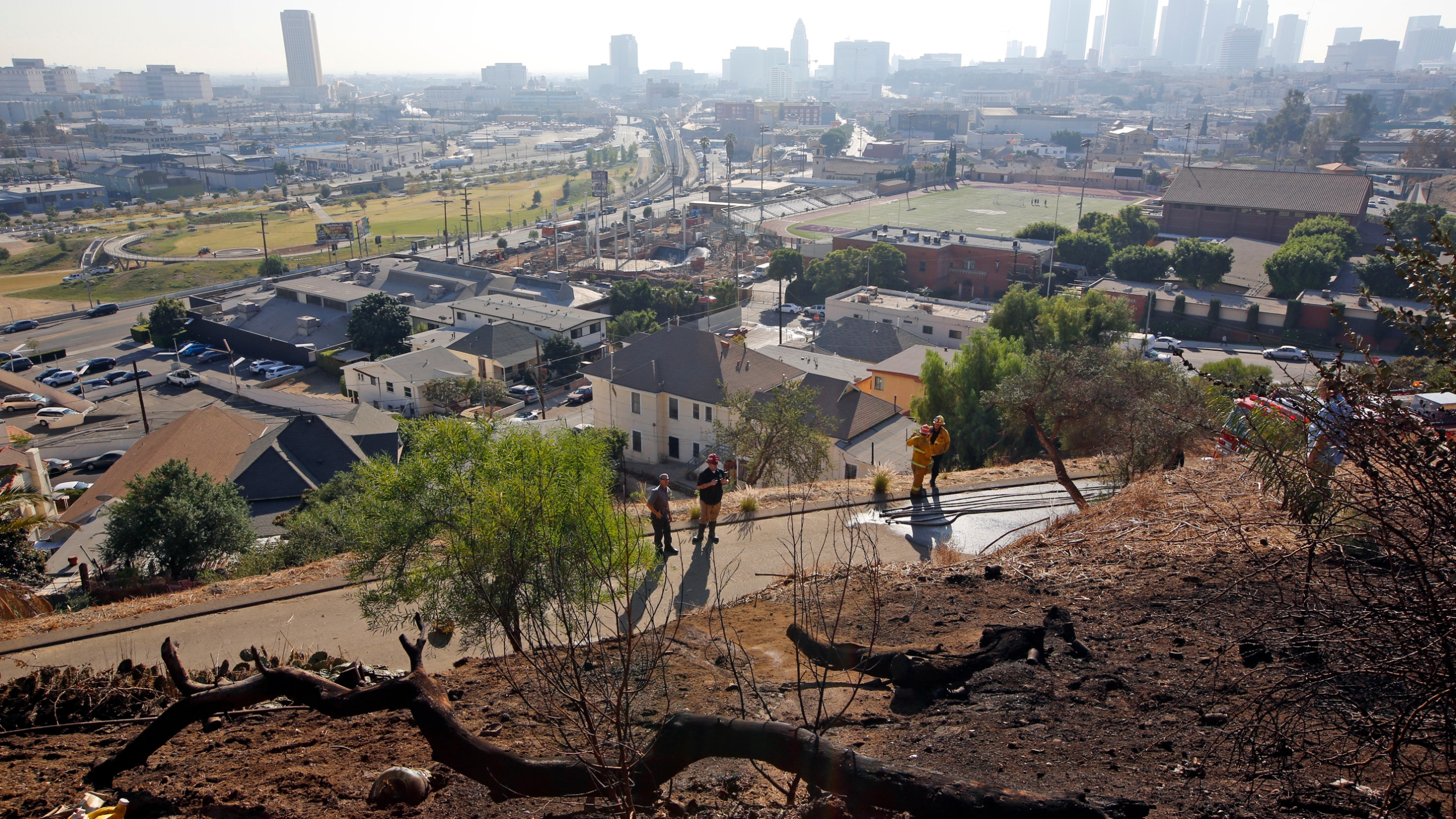 In this Dec. 14, 2017, file photo, Los Angeles Fire Department Arson Counter-Terrorism investigators check a burned-out homeless camp after a brush fire erupted in the hills in Elysian Park near downtown Los Angeles. Authorities say fires linked to homeless tents and camps are raising concern in Los Angeles, where they have claimed seven lives and caused tens of millions of dollars in damage to nearby businesses. The Los Angeles Times says the Fire Department handled 24 such fires a day in the first quarter of this year. (AP Photo/Damian Dovarganes, File)