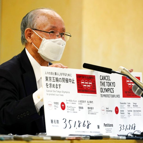 A representative of an anti-Olympics group holds boards showing the current figure of an online petition calling for the cancellation of the Tokyo 2020 Olympics and Paralympics. (AP Photo/Eugene Hoshiko)
