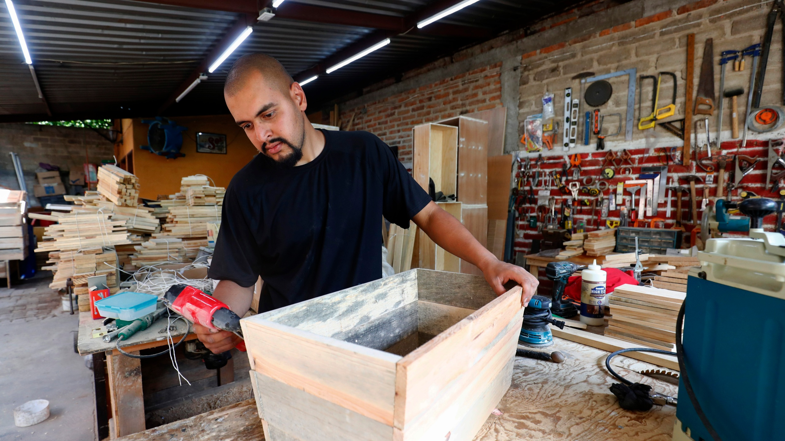 Jesus Lopez works in his family's carpentry workshop in Zapopan, Jalisco state, Thursday, May 13, 2021. Lopez arrived to the U.S. when he was 9 on a tourist visa that later expired. He became a Deferred Action for Childhood Arrivals, DACA, recipient in 2012, which allowed him to work. In 2015, he said he did not complete his DACA renewal because he couldn't afford it. (AP Photo/Refugio Ruiz)