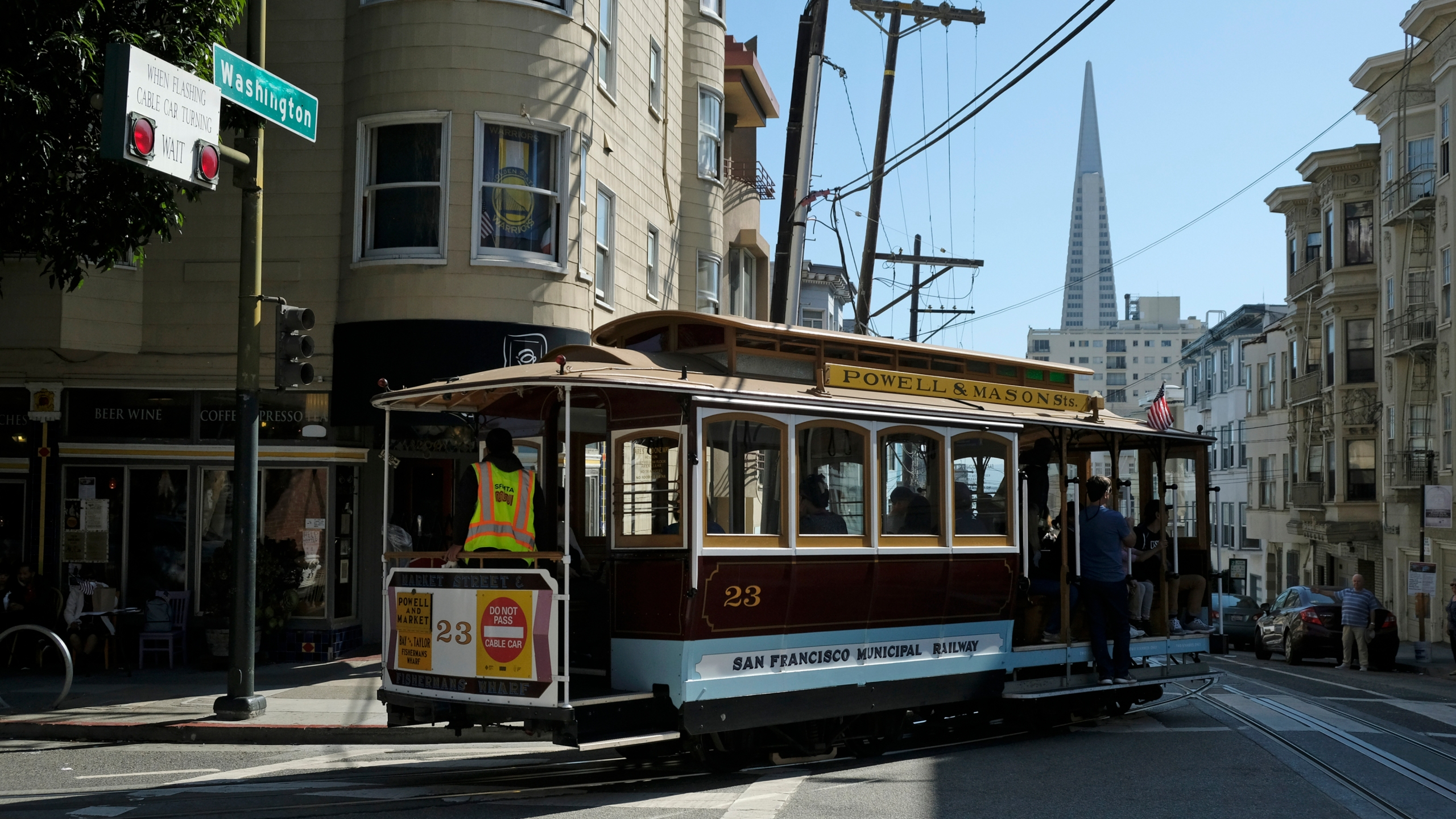 In this Sept. 11, 2019, file photo, a cable car turns onto Washington Street with the Transamerica Pyramid in the background in San Francisco. (AP Photo/Eric Risberg, File)
