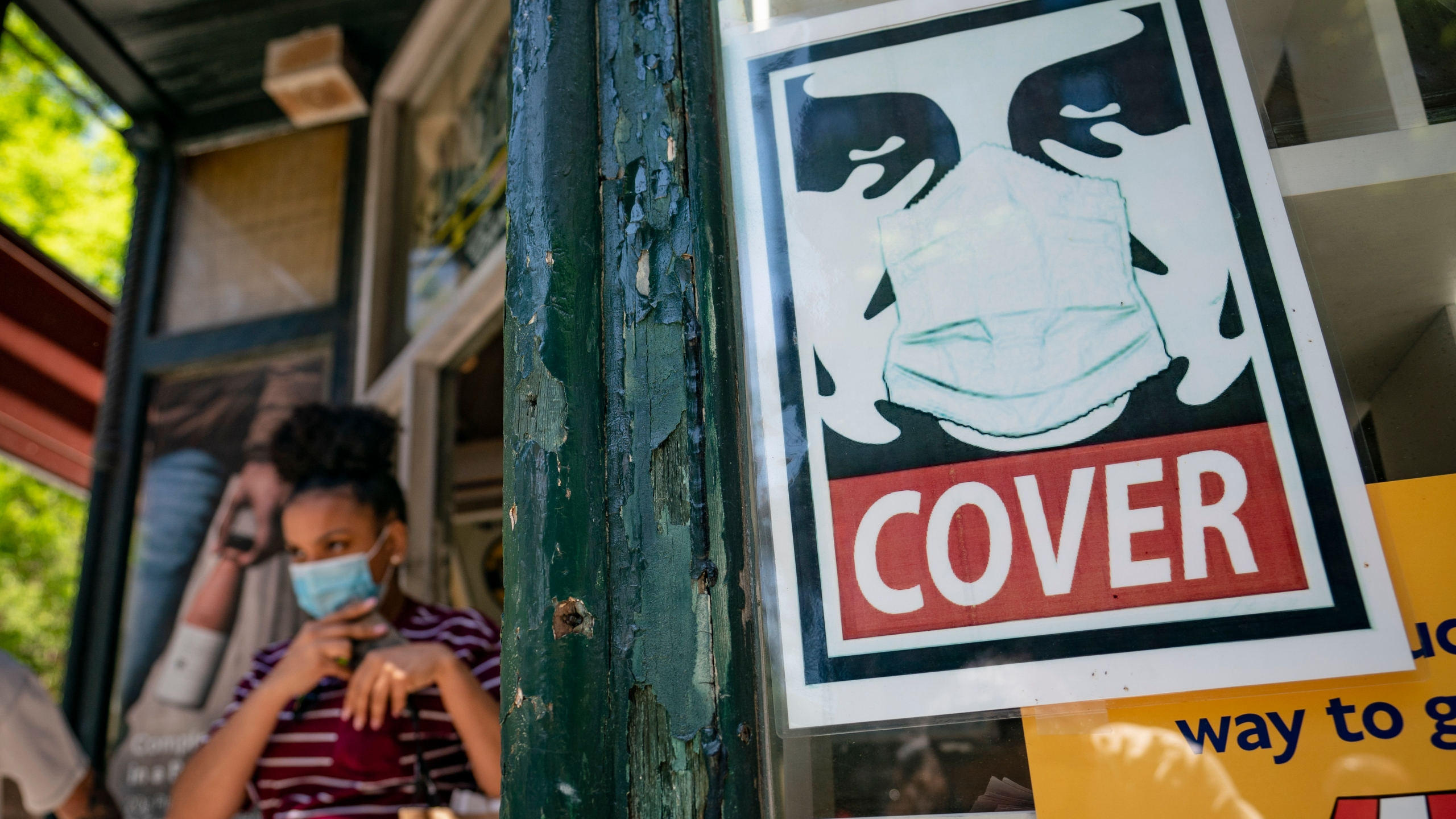 A customer exits a corner market while wearing a protective mask in the retail shopping district of the SoHo neighborhood of the Manhattan borough of New York, Friday, May 14, 2021. (AP Photo/John Minchillo)