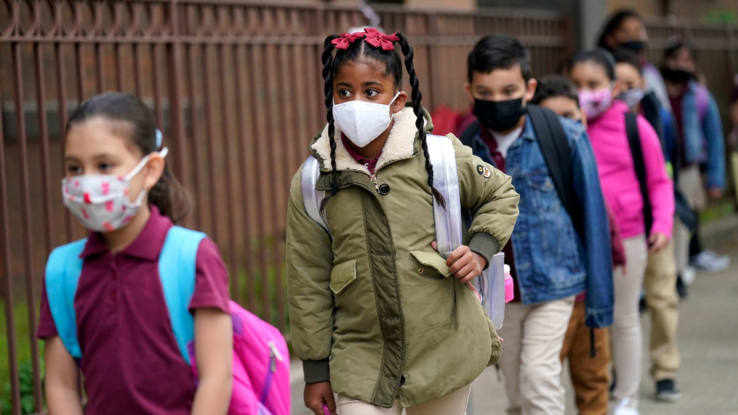 In this April 29, 2021, file photo, students line up to enter Christa McAuliffe School in Jersey City, N.J. Children are having their noses swabbed or saliva sampled at school to test for the coronavirus. As more children return to school buildings this spring, widely varying approaches have emerged on how and whether to test students and staff members for the virus. (AP Photo/Seth Wenig, File)