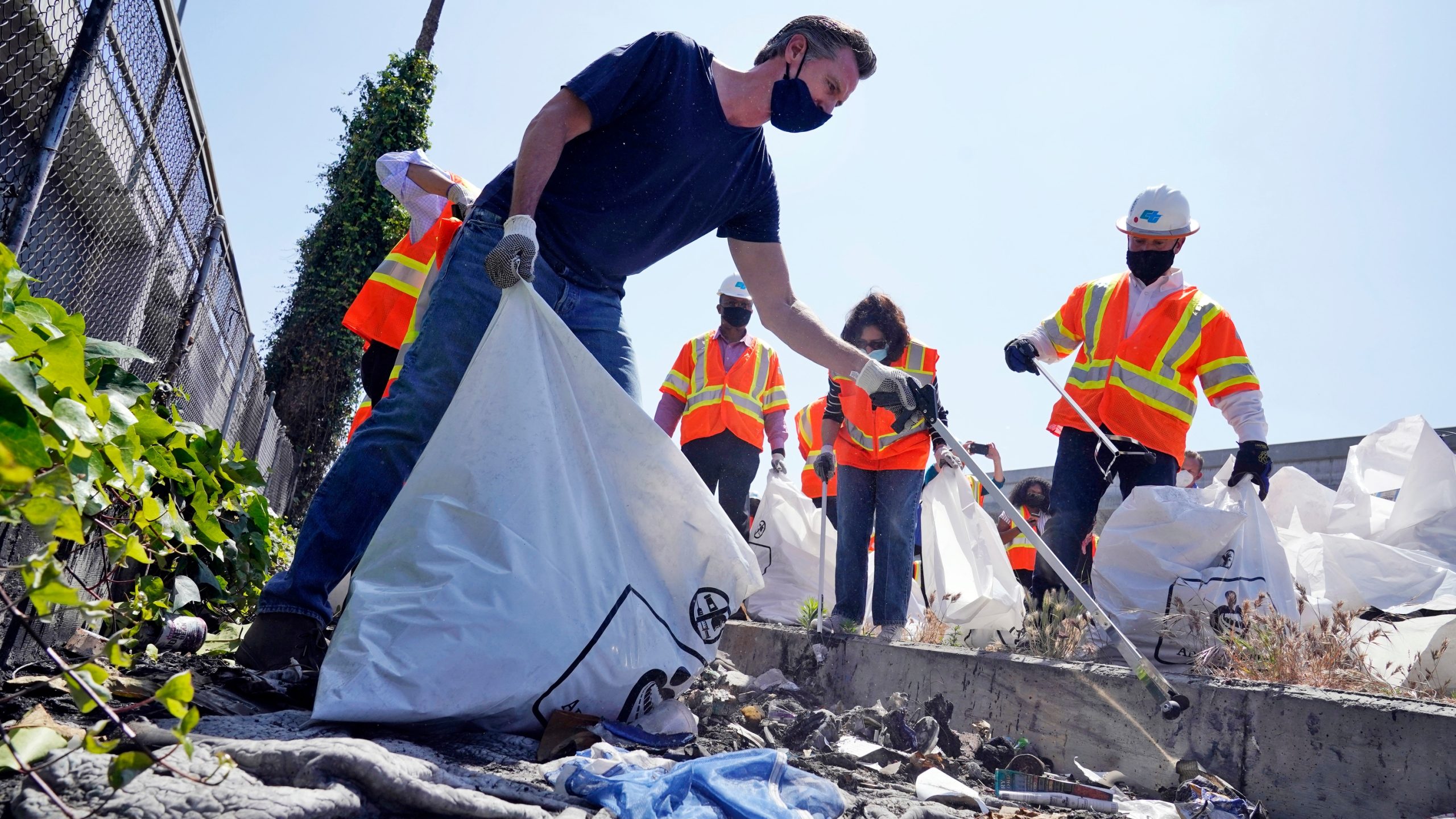 In this Tuesday, May 11, 2021, file photo, California Gov. Gavin Newsom joins a cleanup effort in Los Angeles. (AP Photo/Marcio Jose Sanchez, File)