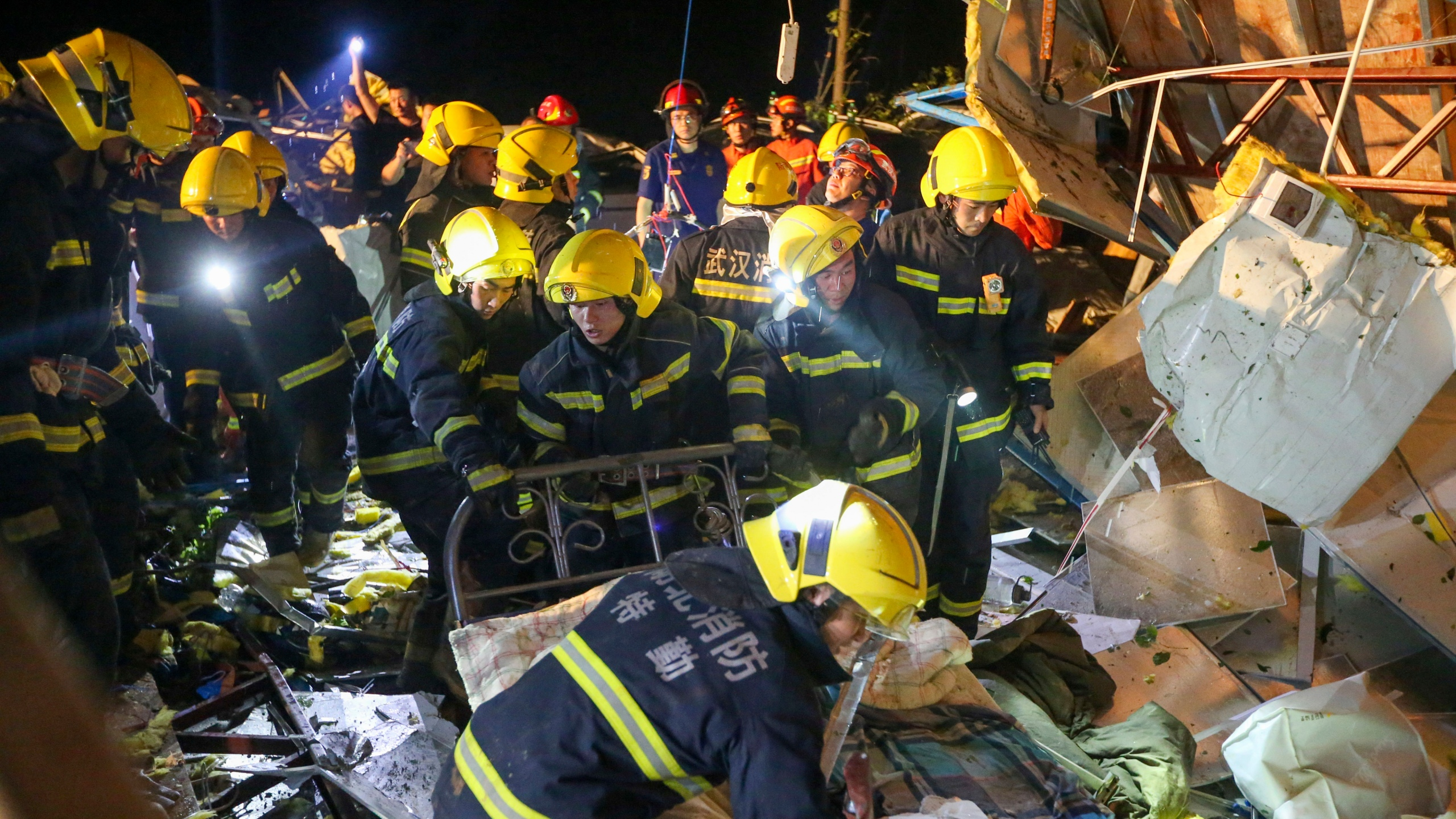 In this photo released by China's Xinhua News Agency, emergency personnel search through the wreckage of buildings destroyed by a reported tornado in Wuhan in central China's Hubei Province, early Saturday, May 15, 2021. Two tornadoes killed several people in central and eastern China and left hundreds of others injured, officials and state media reported Saturday. (Xiong Qi/Xinhua via AP)