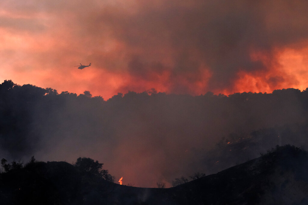 A firefighting helicopter prepares to drop water onto a brush fire scorching at least 100 acres in the Pacific Palisades area of Los Angeles on Saturday, May 15, 2021. (AP Photo/Ringo H.W. Chiu)