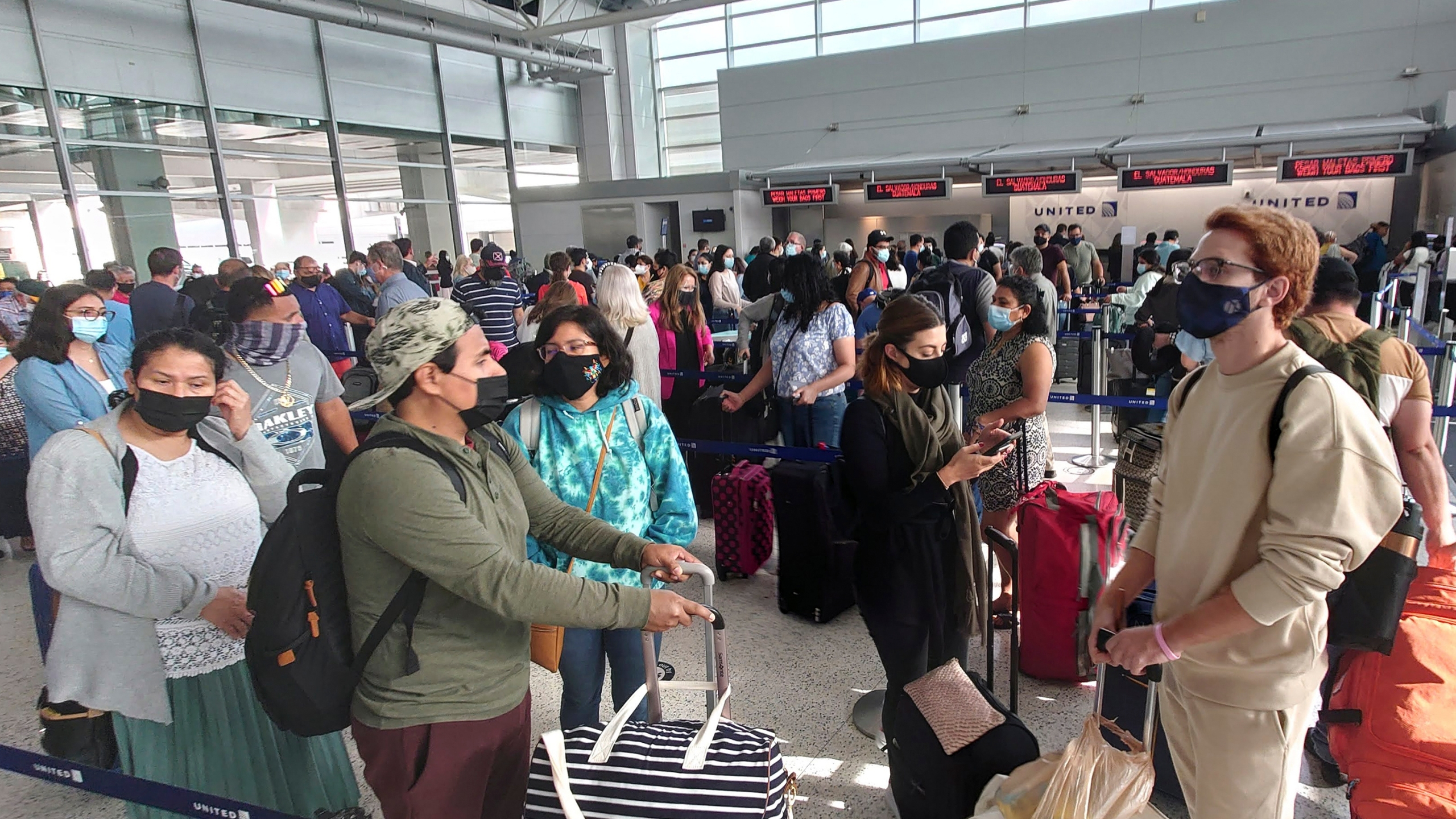 Airline passengers wait to check-in at George Bush Intercontinental Airport Sunday, May 16, 2021, in Houston. (AP Photo/David J. Phillip)
