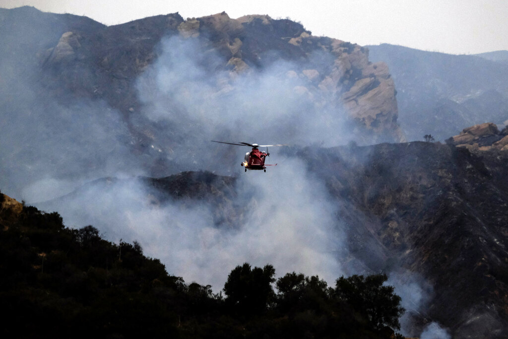 A firefighting helicopter prepares to drop water onto a wildfire in the Pacific Palisades area of Los Angeles, Sunday, May 16, 2021. (AP Photo/Ringo H.W. Chiu)