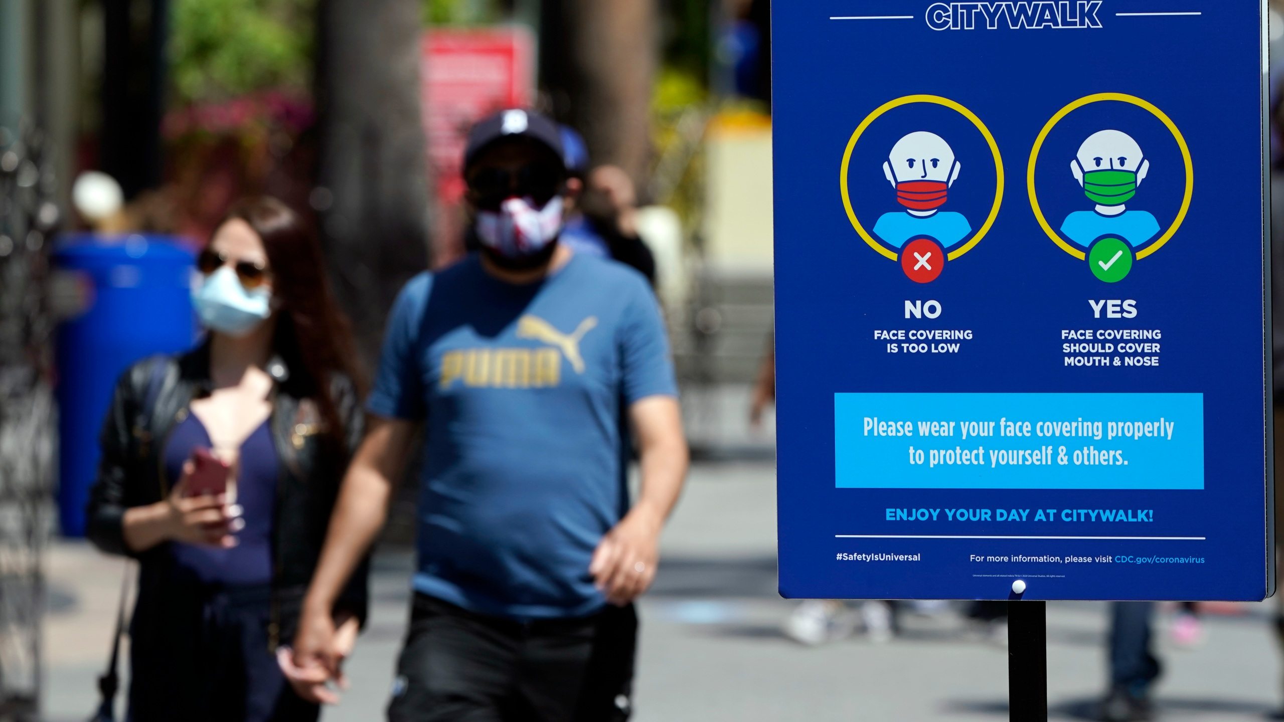 Signs instruct visitors on the proper way to wear masks at the Universal City Walk in Universal Studios in Los Angeles on May 14, 2021. (Marcio Jose Sanchez / Associated Press)