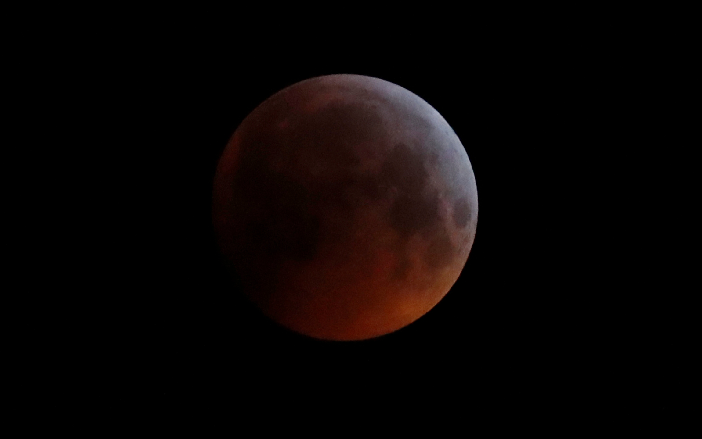 """In this Monday, Jan. 21, 2019 file photo, the Earth's shadow falls across the full moon seen above Brighton, southeast England. The first total lunar eclipse in more than two years coincides with a supermoon this week for a cosmic show. This super """"blood"""" moon will be visible Wednesday, May 26, 2021 across the Pacific _ offering the best viewing _ as well as the western half of North America, bottom of South America and eastern Asia. (AP Photo/Alastair Grant, File)"""