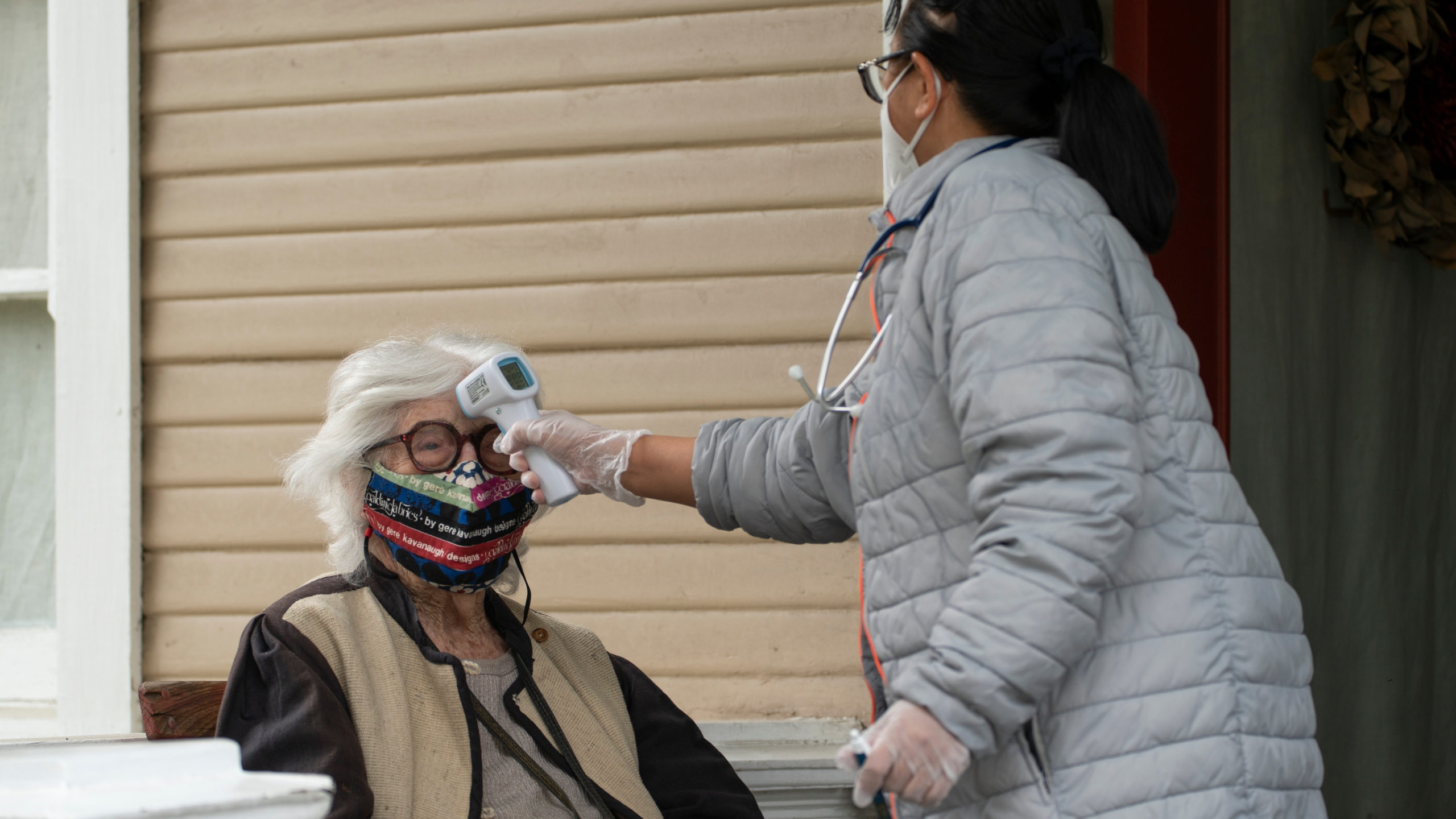 Designer Gere Kavanaugh, left, wears a face mask of her design in the Echo Park neighborhood of Los Angeles, Monday, May 17, 2021. At right, Silver Age Home Health licensed vocational nurse Daisy Cabaluna monitors her temperature during a weekly outdoors visit at her home. California is keeping its rules for wearing face masks in place until the state more broadly lifts its pandemic restrictions on June 15. (AP Photo/Damian Dovarganes)