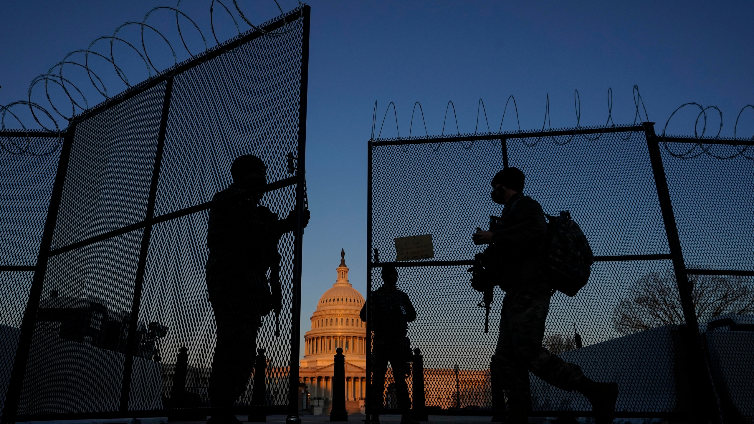 In this March 8, 2021, file photo, members of the National Guard open a gate in the razor wire topped perimeter fence around the Capitol at sunrise in Washington. (AP Photo/Carolyn Kaster, File)