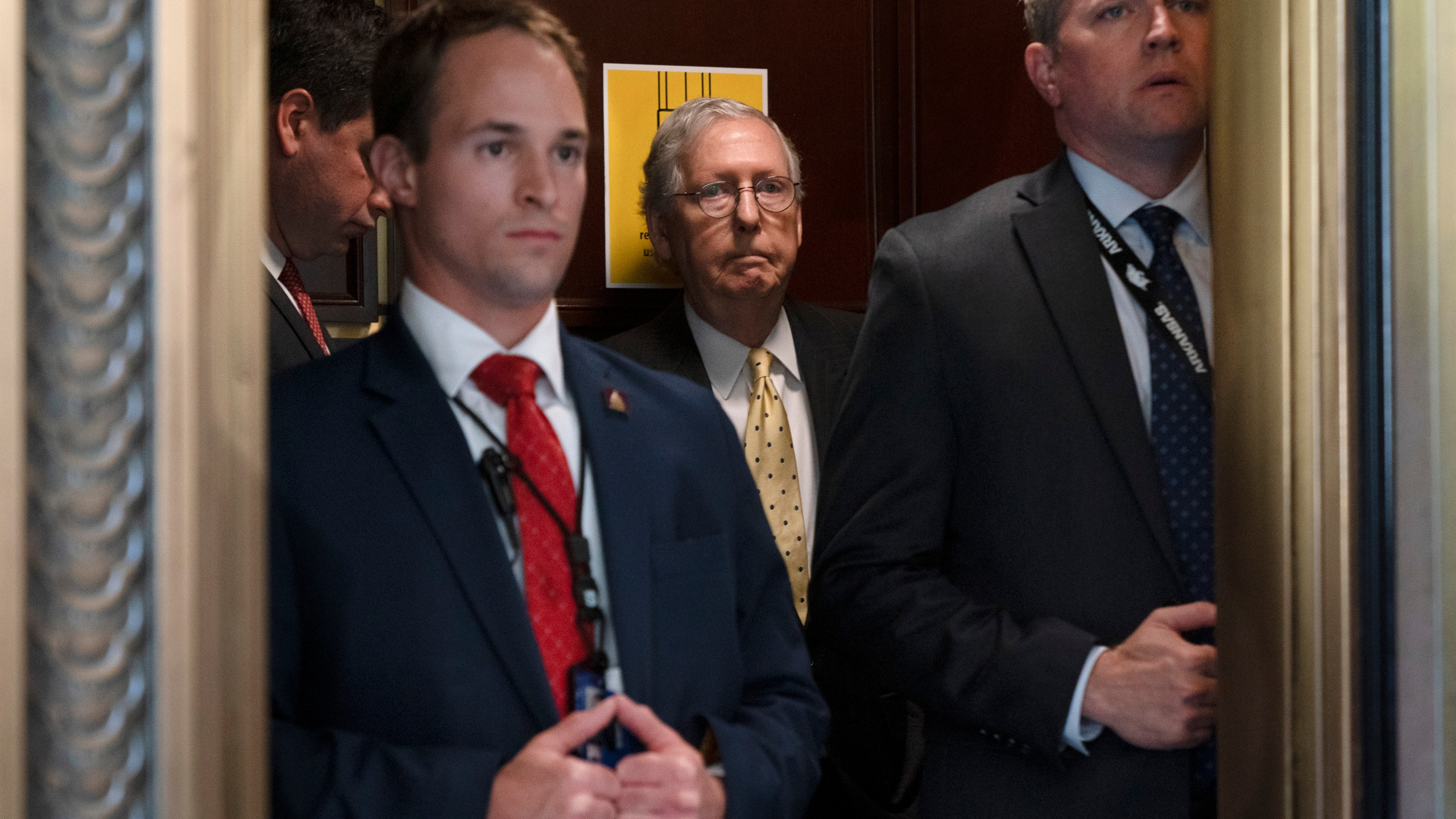 Senate Minority Leader Mitch McConnell of Ky., center, takes an elevator, Tuesday, May 18, 2021, after a meeting with Senate Republicans on Capitol Hill in Washington. (AP Photo/Jacquelyn Martin)