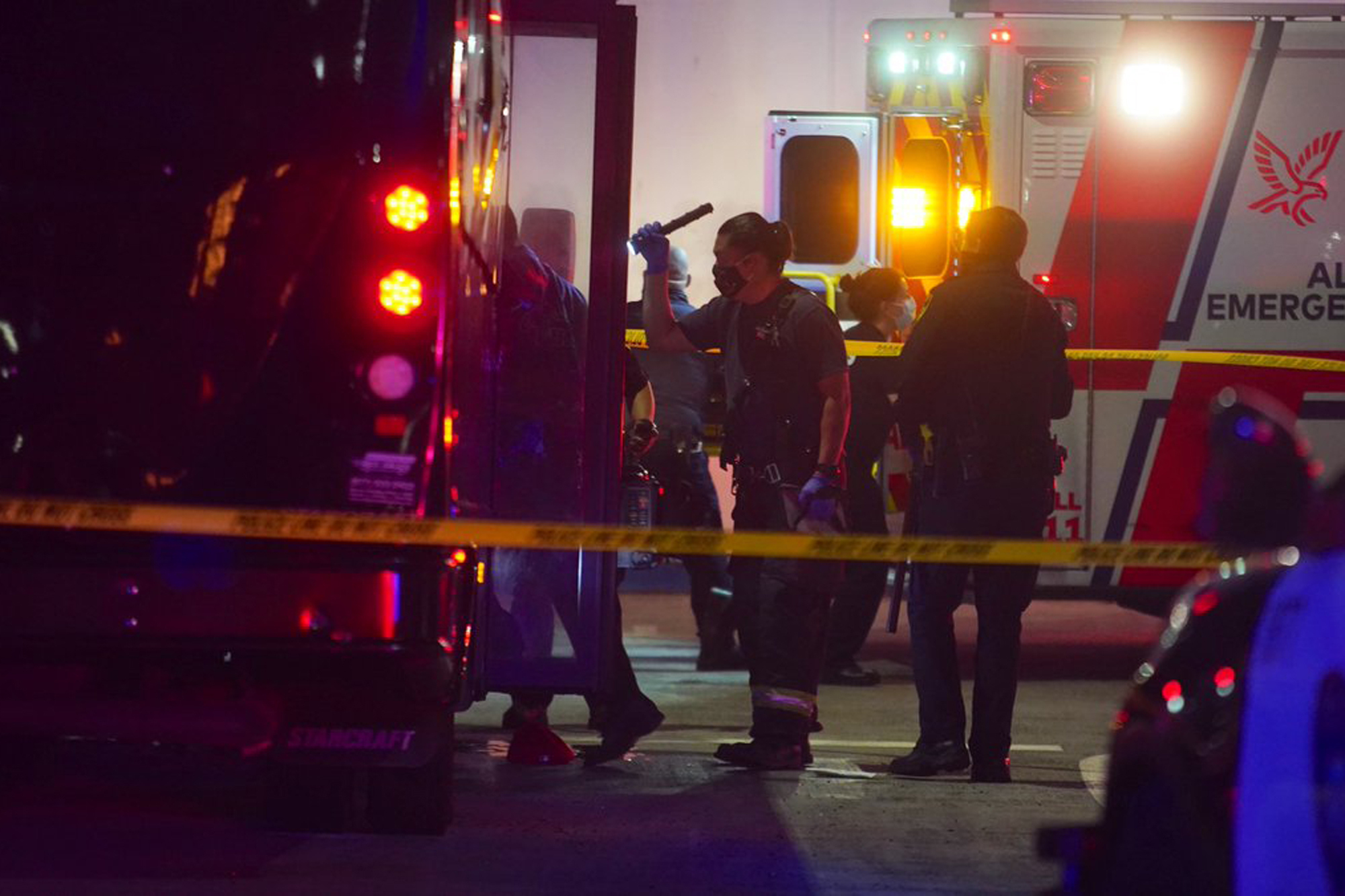 Oakland police and fire attend to multiple people who were injured in a shooting involving a party bus in East Oakland, Calif., on Tuesday, May 18, 2021. Someone opened fire on a party bus on a San Francisco Bay Area freeway early Tuesday, killing two women and wounding at least five others, authorities said. The passengers were celebrating a woman's 21st birthday when the bus was attacked on Interstate 580 as it was returning to Oakland from San Francisco, the East Bay Times reported. (Dylan Bouscher/Bay Area News Group via AP)