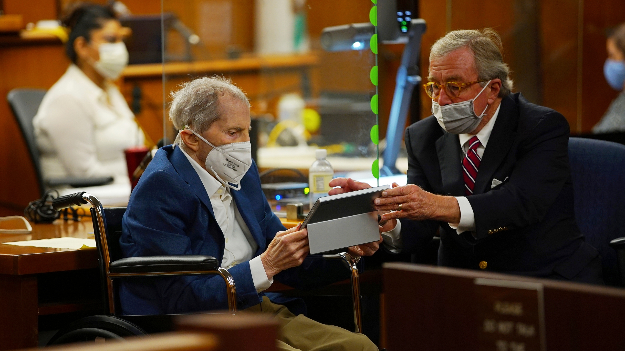 Defense attorney Dick DeGuerin, right, gives Robert Durst a device to read the real time spoken script as he appears in a courtroom as Judge Mark E. Windham gives last instructions to jurors before attorneys begin opening statements at the Los Angeles County Superior Court on May 18, 2021. (Al Seib/Los Angeles Times)