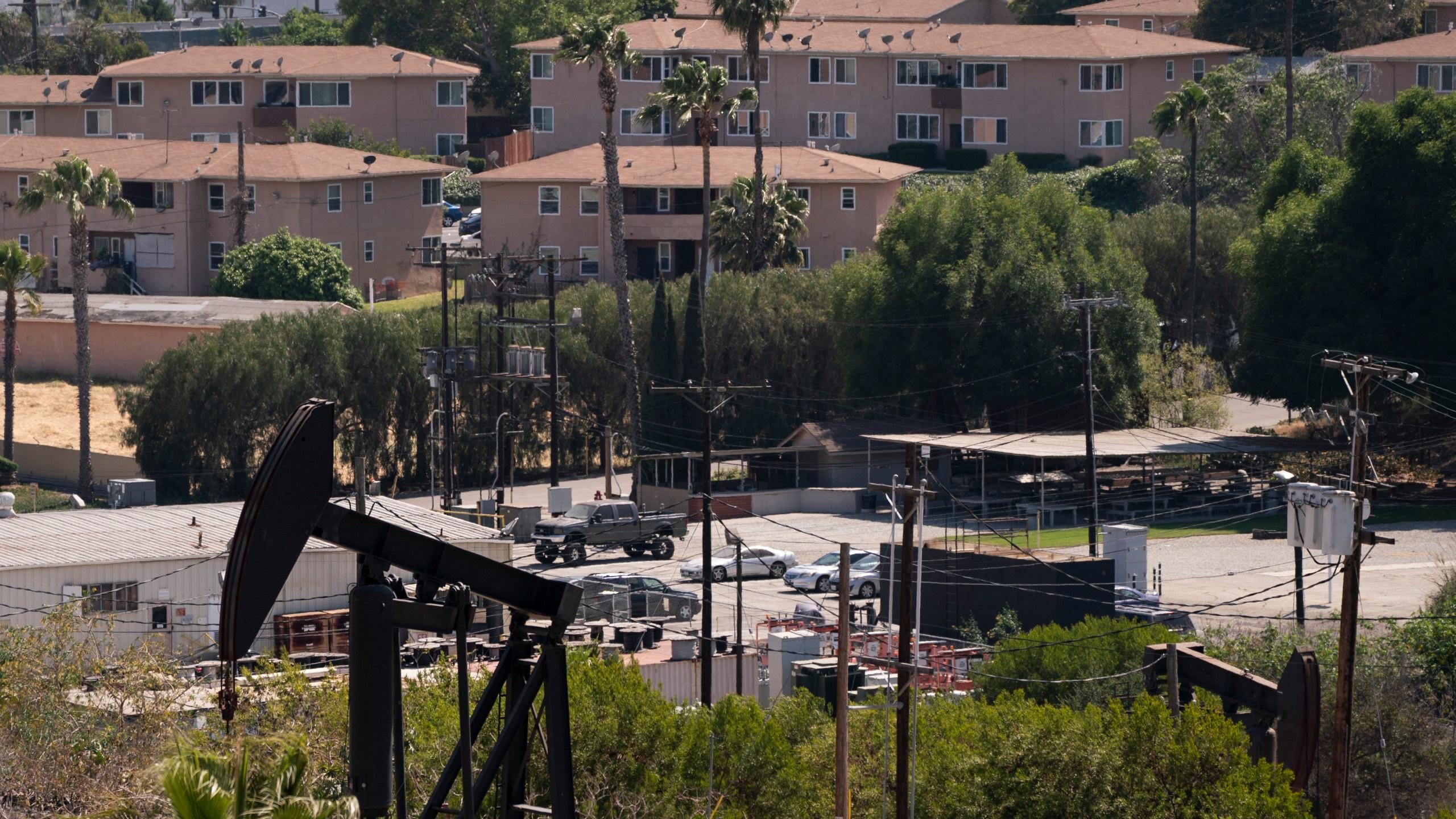 Apartment buildings are seen behind pump jacks operating at the Inglewood Oil Field in Los Angeles, Tuesday, May 18, 2021. (AP Photo/Jae C. Hong)