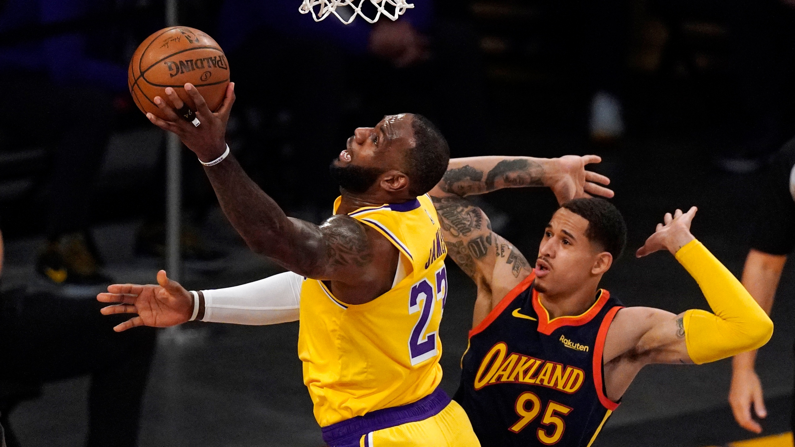 Los Angeles Lakers forward LeBron James, left, shoots as Golden State Warriors forward Juan Toscano-Anderson defends during the first half of an NBA basketball Western Conference Play-In game on May 19, 2021, in Los Angeles. (AP Photo/Mark J. Terrill)
