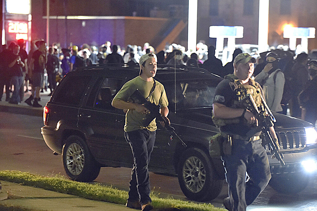In this Aug. 25, 2020 file photo, Kyle Rittenhouse, left, with backwards cap, walks along Sheridan Road in Kenosha, Wis., with another armed civilian. (Adam Rogan/The Journal Times via AP, File)