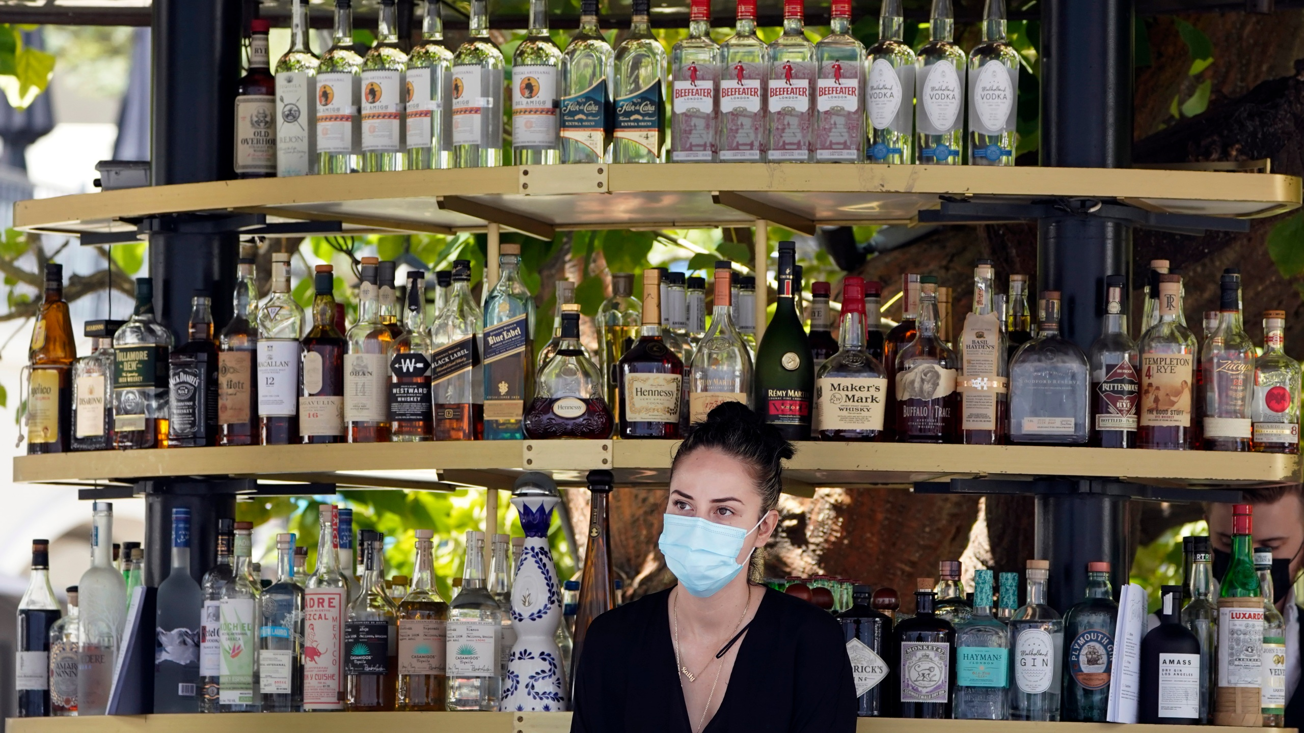 A bartender wears a mask while working at an outdoor bar amid the COVID-19 pandemic Thursday, May 20, 2021, at The Grove in Los Angeles. California regulators will shoot for a mid-June easing of workplace masking and social distancing requirements to conform with a broader state order. They asked to delay a debate Thursday on how quickly they should drop coronavirus safety rules for employees. (AP Photo/Marcio Jose Sanchez)