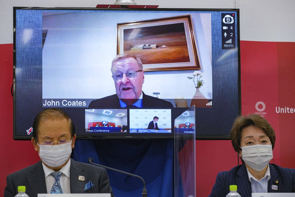CEO of the Tokyo 2020 Toshiro Muto, left, and President of the Tokyo 2020 Seiko Hashimoto, right, listen to Chairman of the Coordination Commission for the Games of the XXXII Olympiad Tokyo 2020 John Coates, (on screen), delivering a speech during the Tokyo 2020 IOC Coordination Commission press conference on Friday, May 21, 2021 in Tokyo. (Nicolas Datiche/Pool Photo via AP)