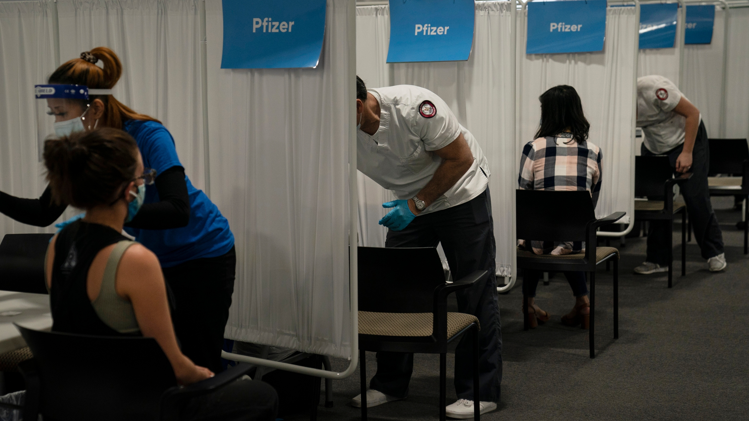 Student nurse Dario Gomez, center, disinfects a chair after administering the Pfizer COVID-19 vaccine to a patient at Providence Edwards Lifesciences vaccination site in Santa Ana on May 21, 2021. (Jae C. Hong/Associated Press)