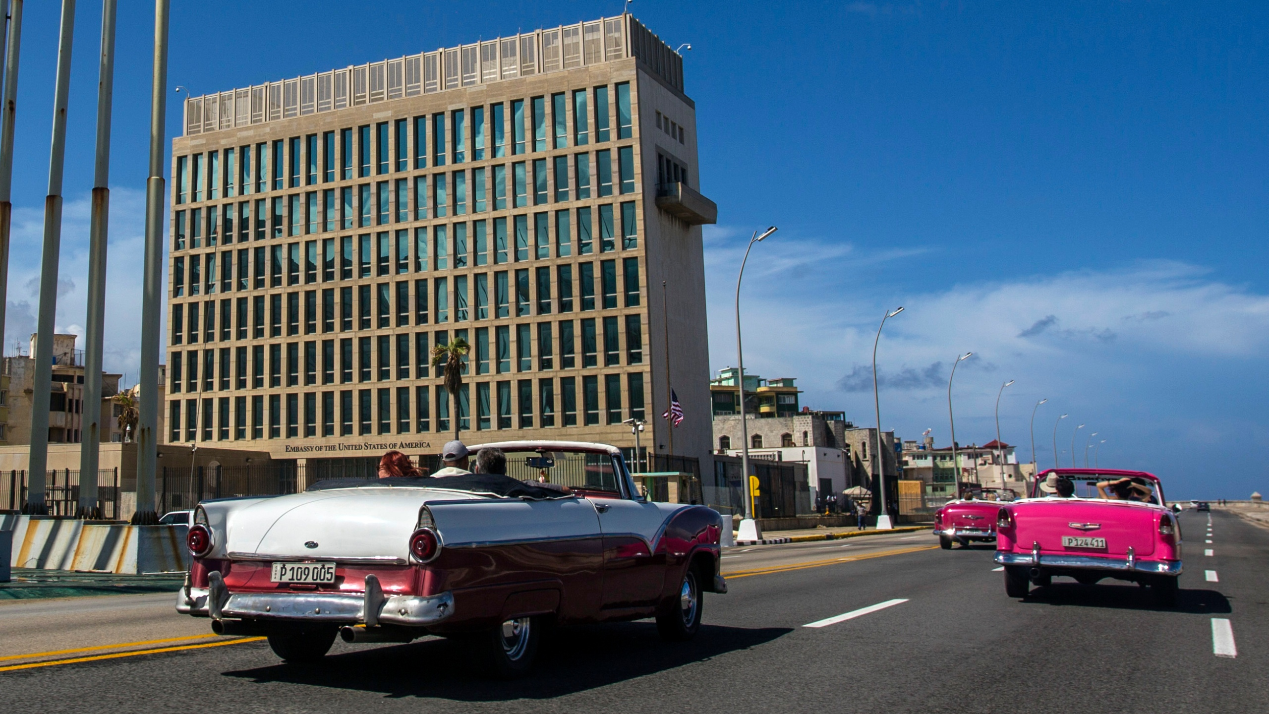 In this Oct. 3, 2017, file photo, tourists ride classic convertible cars on the Malecon beside the United States Embassy in Havana, Cuba. (AP Photo/Desmond Boylan, File)