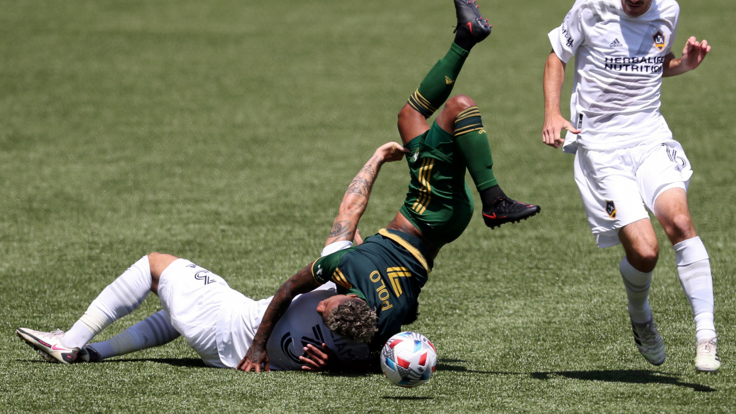 Portland Timbers midfielder Andy Polo (7) flips over Los Angeles Galaxy defender Derrick Williams (3) as L.A. Galaxy midfielder Sacha Kljestan (16) runs alongside them during the first half of an MLS soccer match on May 22, 2021, in Portland, Ore. Williams received a red card for the foul. (Amanda Loman / Associated Press)