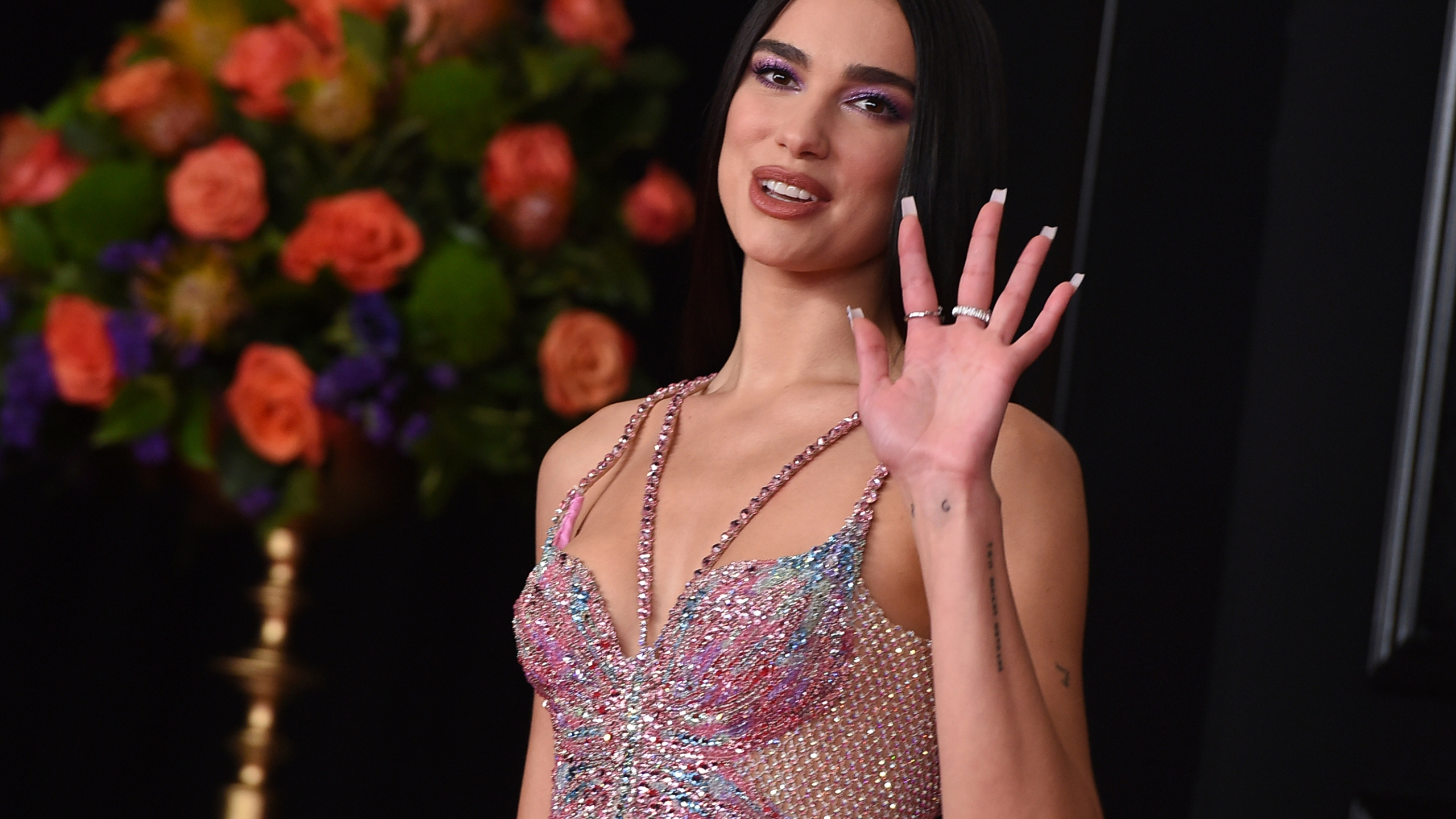 """In this Sunday, March 14, 2021 file photo, Dua Lipa arrives at the 63rd annual Grammy Awards at the Los Angeles Convention Center. Singer Dua Lipa is blasting the organization which paid for a full-page ad in The New York Times that called her antisemitic for her support of Palestinians, saying it used her name """"shamelessly"""" to """"advance their ugly campaign with falsehoods and blatant misrepresentations."""" Lipa took to Twitter on Saturday, May 22, 2021 to """"reject the false and appalling allegations"""" and said the World Values Network twisted what she stands for. """"I stand in solidarity with all oppressed people and reject all forms of racism,"""" she wrote. (Photo by Jordan Strauss/Invision/AP, File)"""