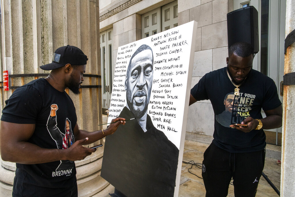 Artist Dennis Owes, 31, from Ghana gives the last touch to his portrait of George Floyd during a rally on Sunday, May 23, 2021, in Brooklyn borough of New York. (AP Photo/Eduardo Munoz Alvarez)