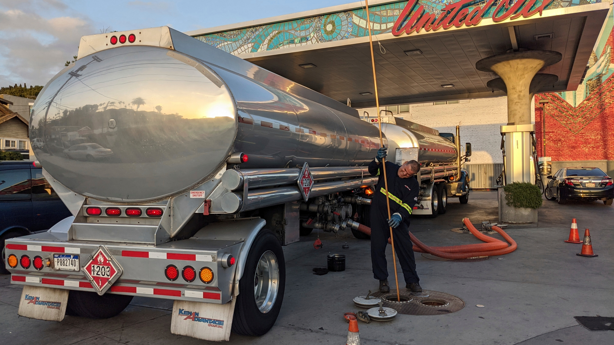 In this May 20, 2021 photo, a fuel truck driver checks the gasoline tank level at a United Oil gas station in Sunset Blvd., in Los Angeles. (AP Photo/Damian Dovarganes)