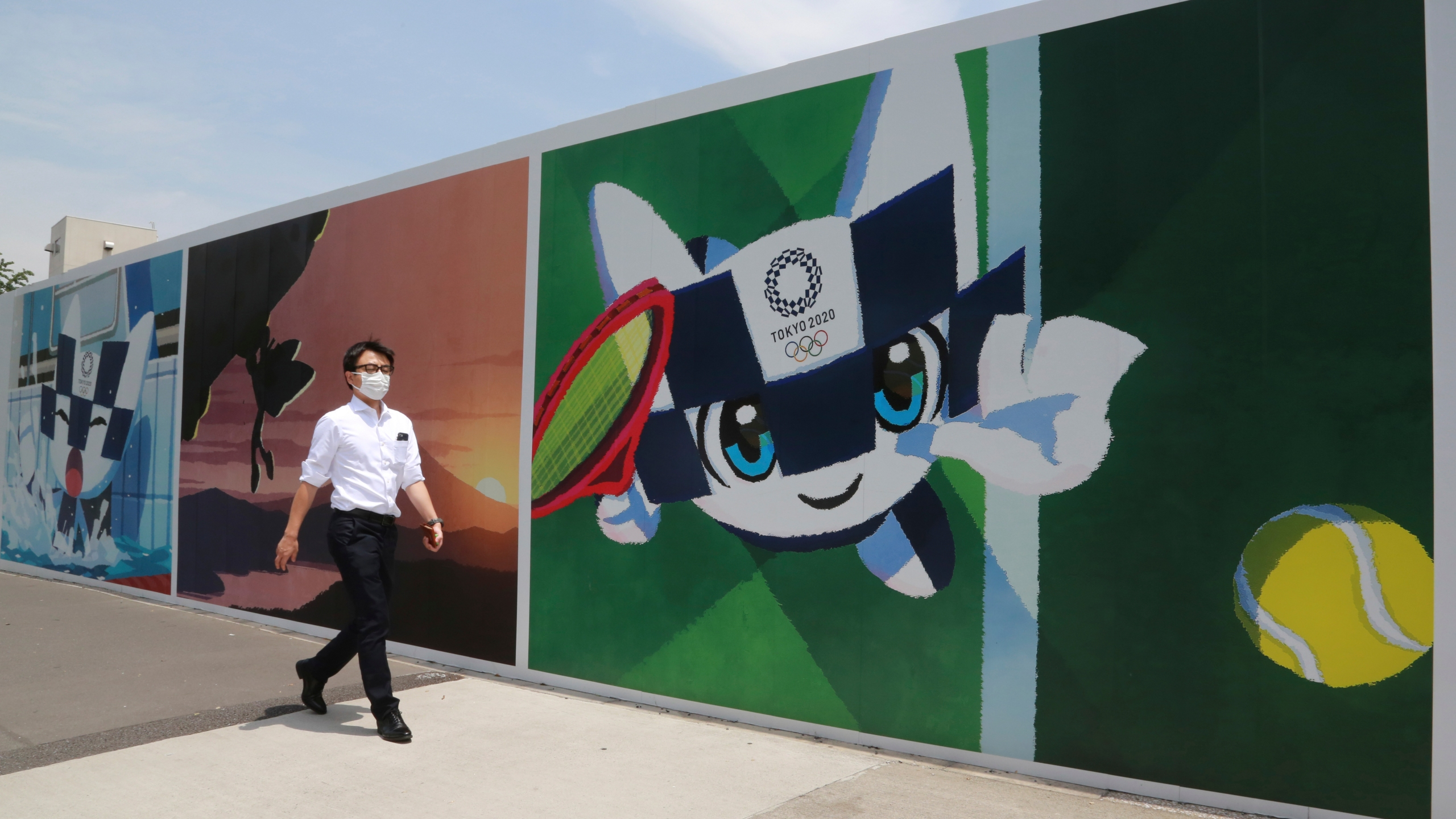 A man walks by posters promoting the Olympic Games planned to start in the summer of 2021, in Tokyo, Monday, May 24, 2021. (AP Photo/Koji Sasahara)