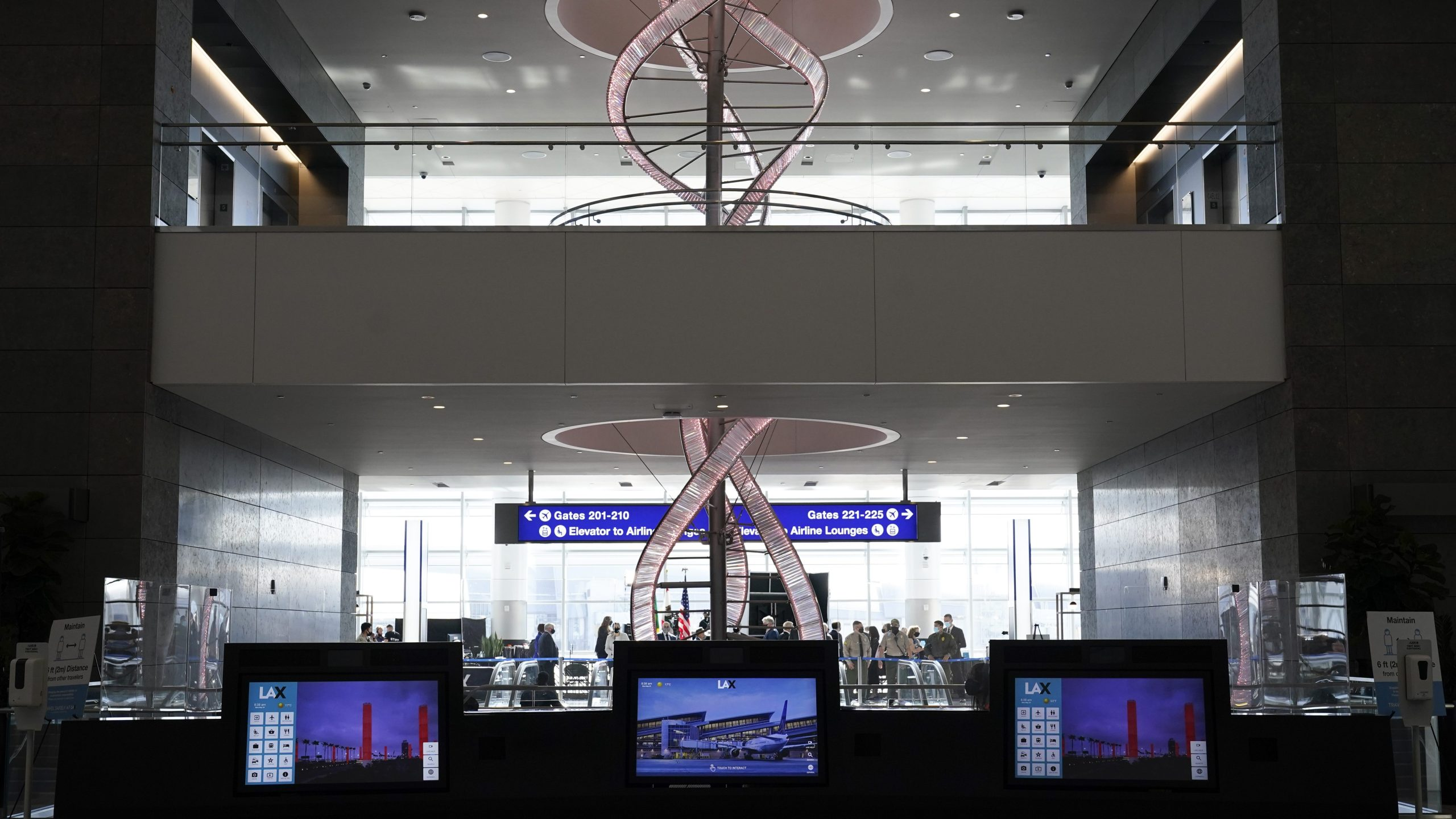 A chandelier hangs behind interactive kiosks at the new West Gates at Tom Bradley International Terminal at Los Angeles International Airport on May 24, 2021. (Ashley Landis / Associated Press)