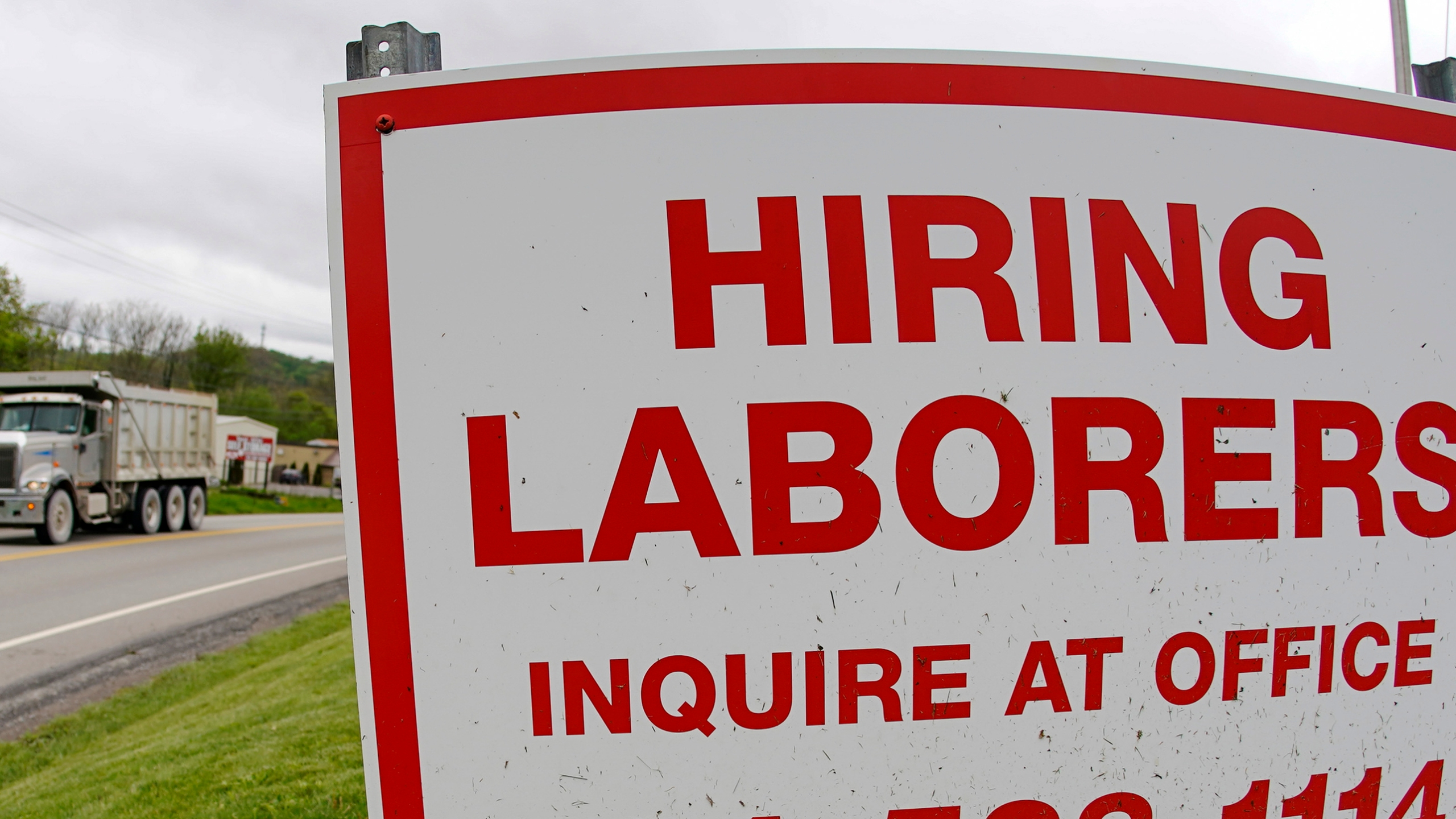In this file photo from May 5, 2021, a truck passes a sign showing a need to hire laborers outside a concrete products company in Evans City, Pa. Pennsylvania will resume work search requirements in July for hundreds of thousands of people receiving unemployment compensation, a top Wolf administration official said Monday, May 24, 2021. (AP Photo/Keith Srakocic, File)